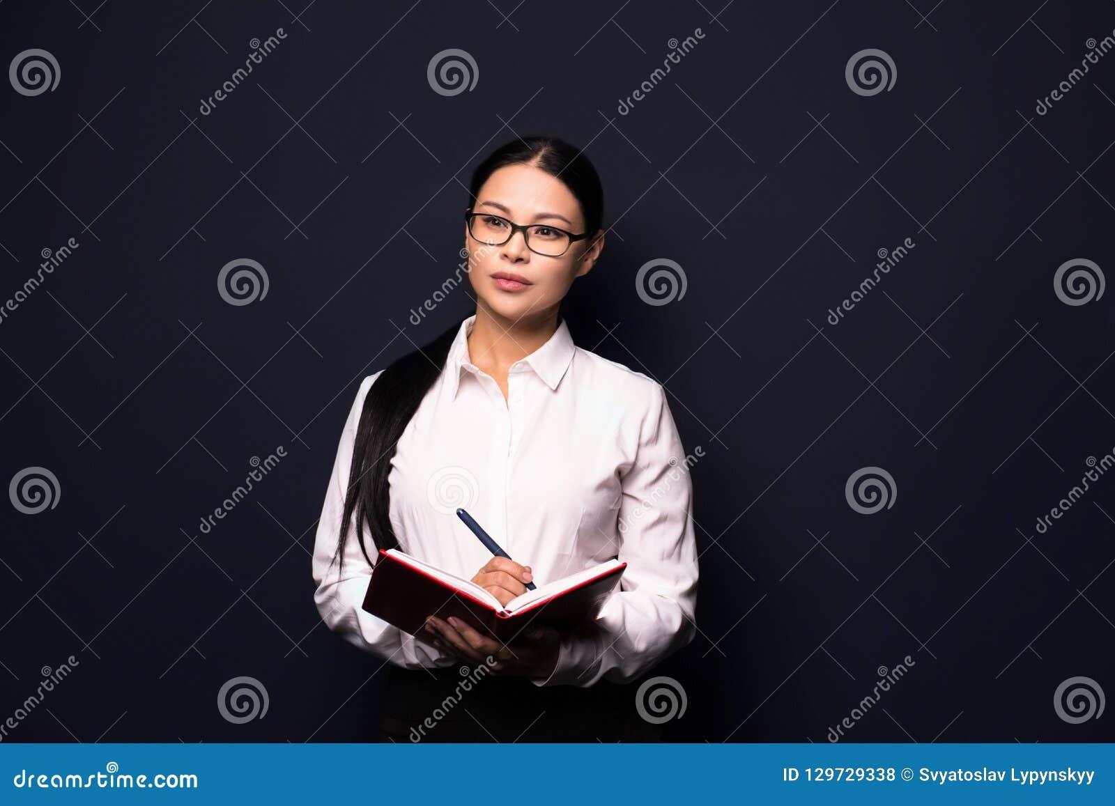 Jonge mooie bedrijfsvrouw die nota s maken
