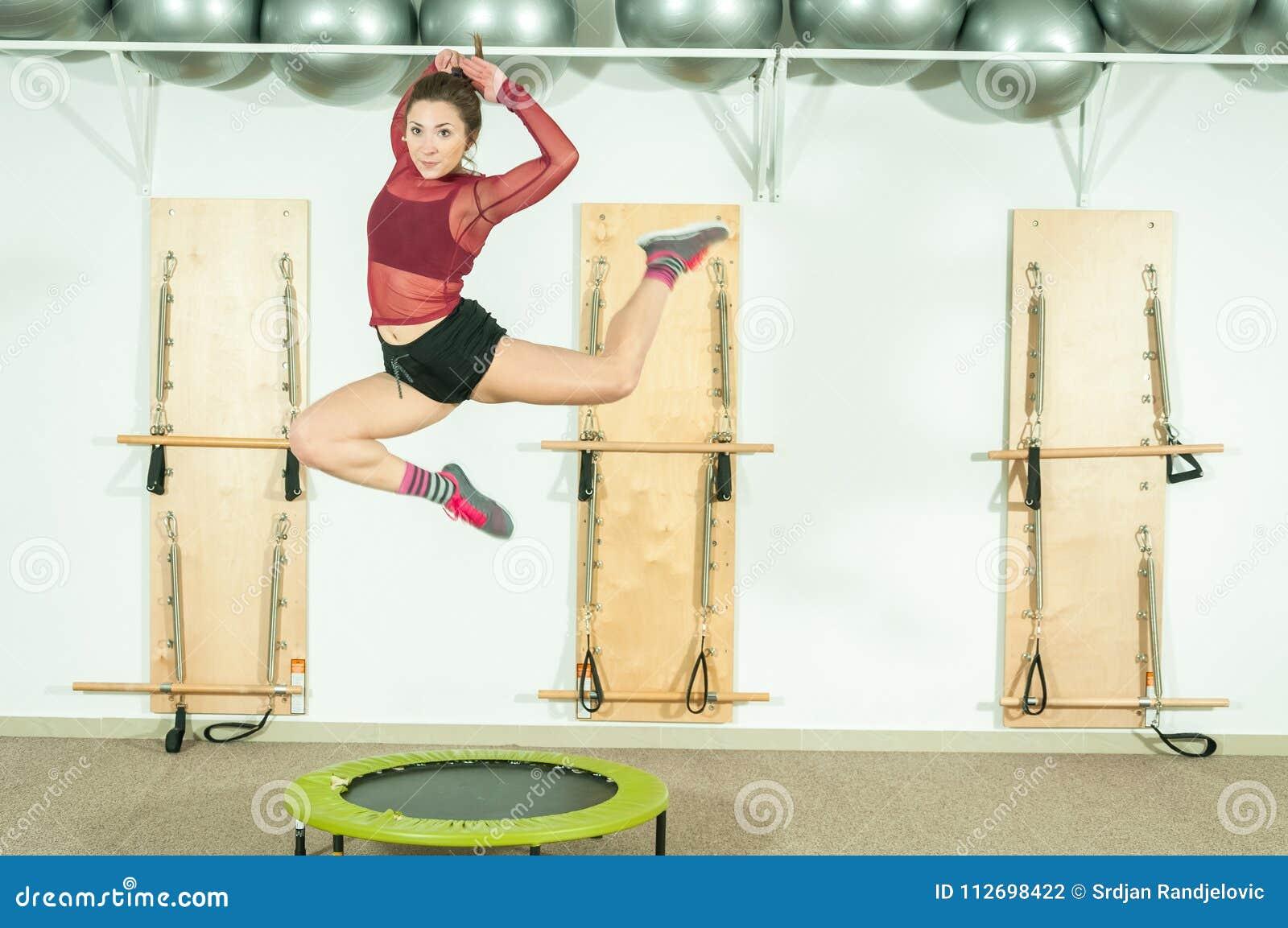 Jonge mooie en aantrekkelijke meisjessprong op de trampoline, selectieve nadruk met motieonduidelijk beeld