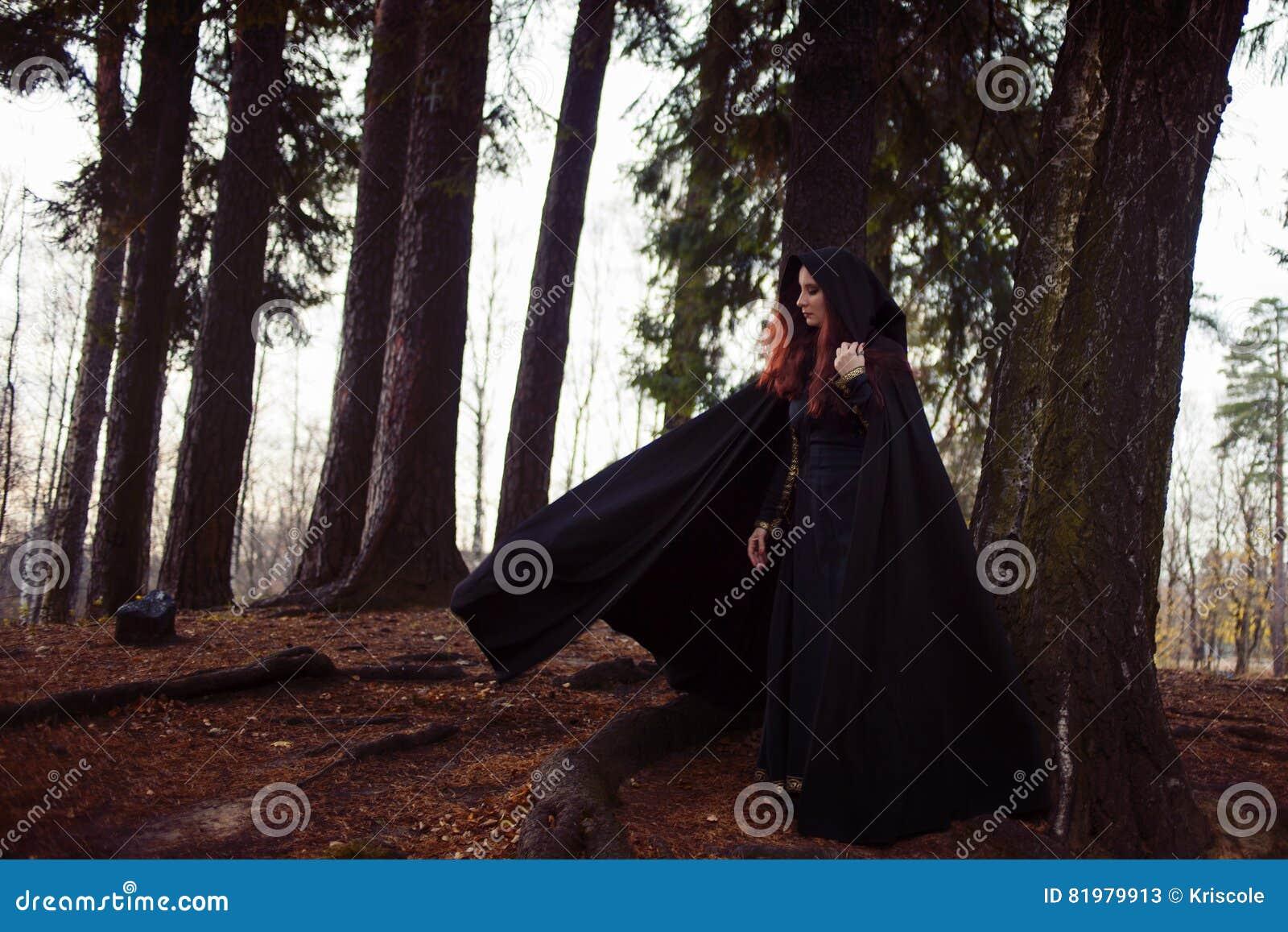 Jonge mooie en geheimzinnige vrouw in hout, in zwarte mantel met kap, beeld van boself of heks