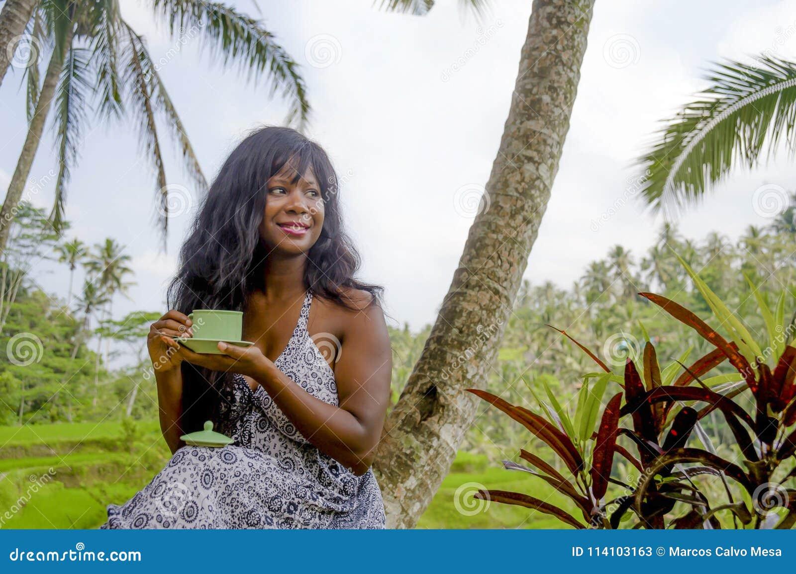 Jonge mooie en gelukkige zwarte de vrouw van de afro Amerikaanse toerist het drinken koffie of thee het bezoeken wildernisaanplan