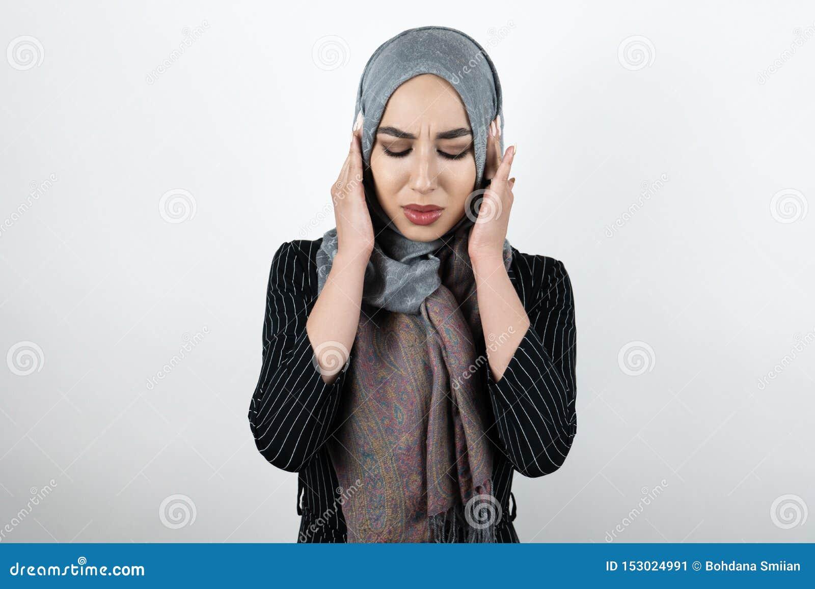 Jonge mooie geïrriteerde Moslimvrouw die tulband dragen hijab, headscarf kijkend boos met haar handen die oren sluiten