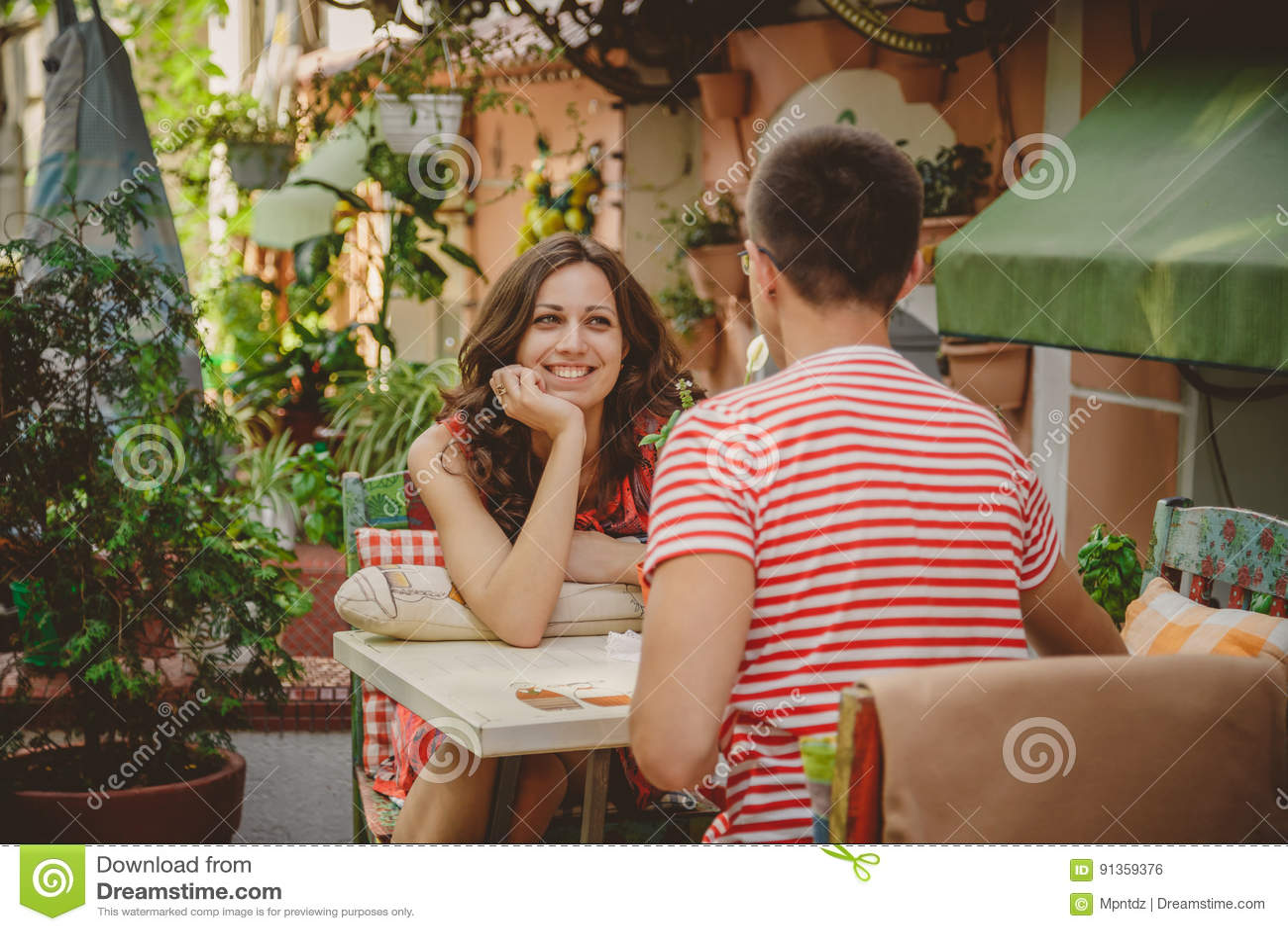 Jonge mooie gelukkige het houden van paarzitting bij straat openluchtkoffie die elkaar bekijken Begin van liefdeverhaal verhoudin