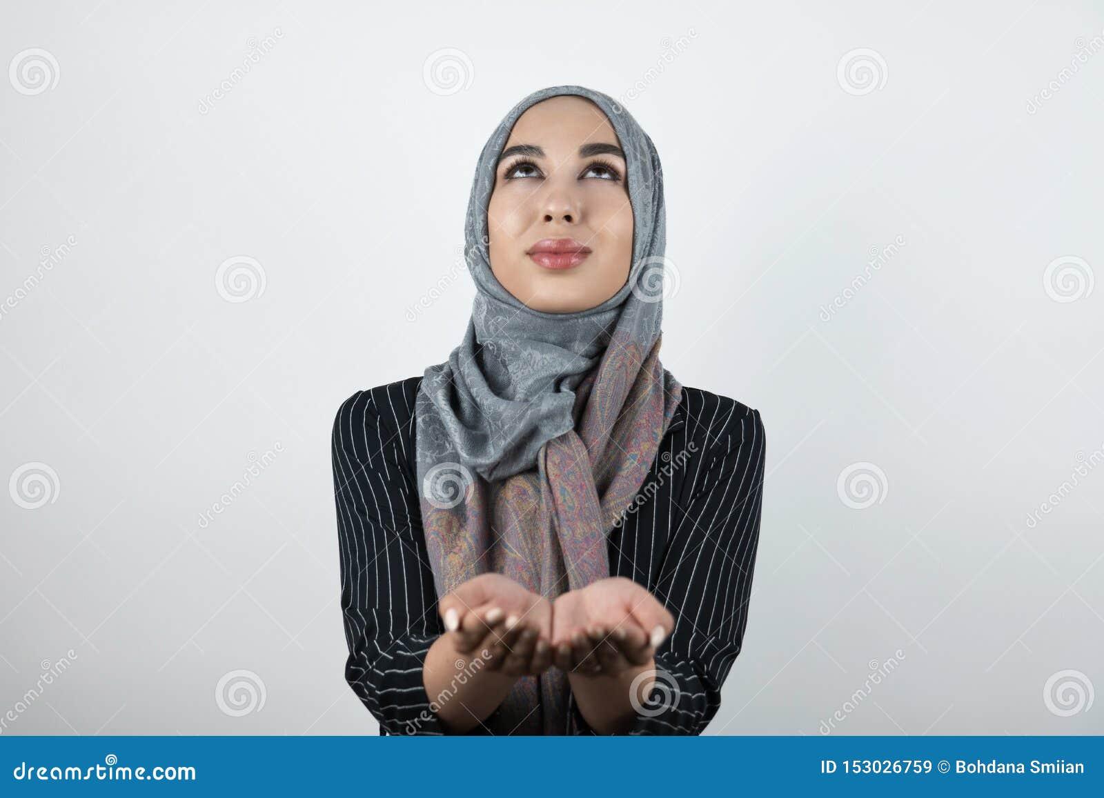 Jonge mooie hoopvolle Moslimvrouw die tulband dragen hijab, headscarf houdend haar handen kijkend omhoog samen geïsoleerd