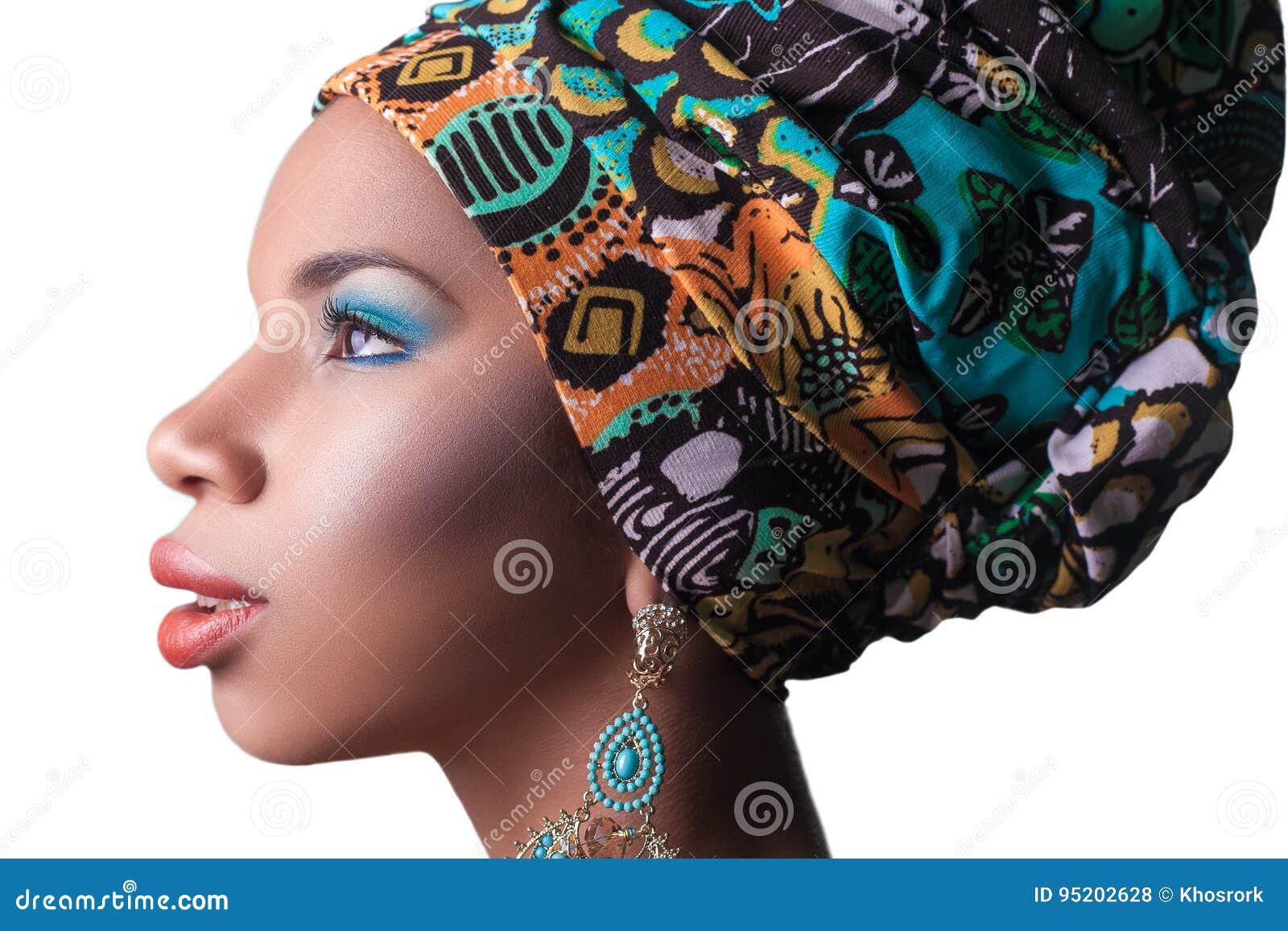 Jonge mooie mannequin met traditionele Afrikaanse stijl met sjaal, oorringen en make-up op oranje achtergrond