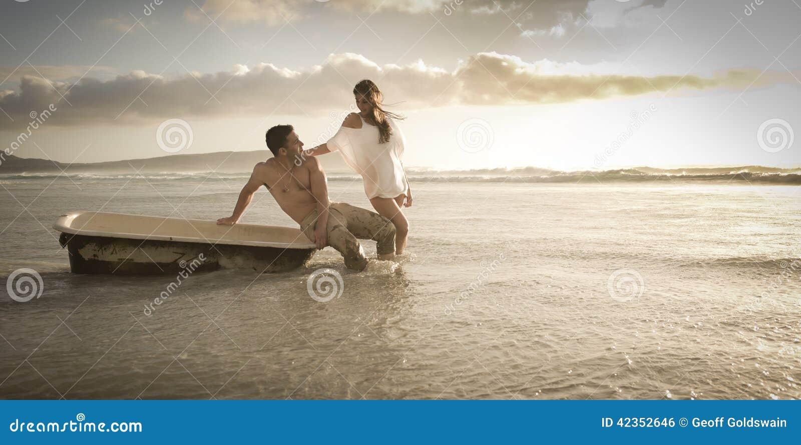 Jonge mooie paar het besteden middag op strand met oude badton