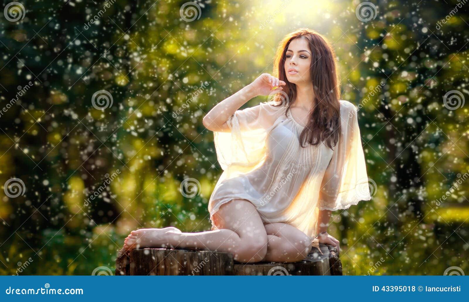 Jonge mooie rode haarvrouw die het transparante witte blouse stellen op een stomp in een groen bos Modieus sexy meisje dragen