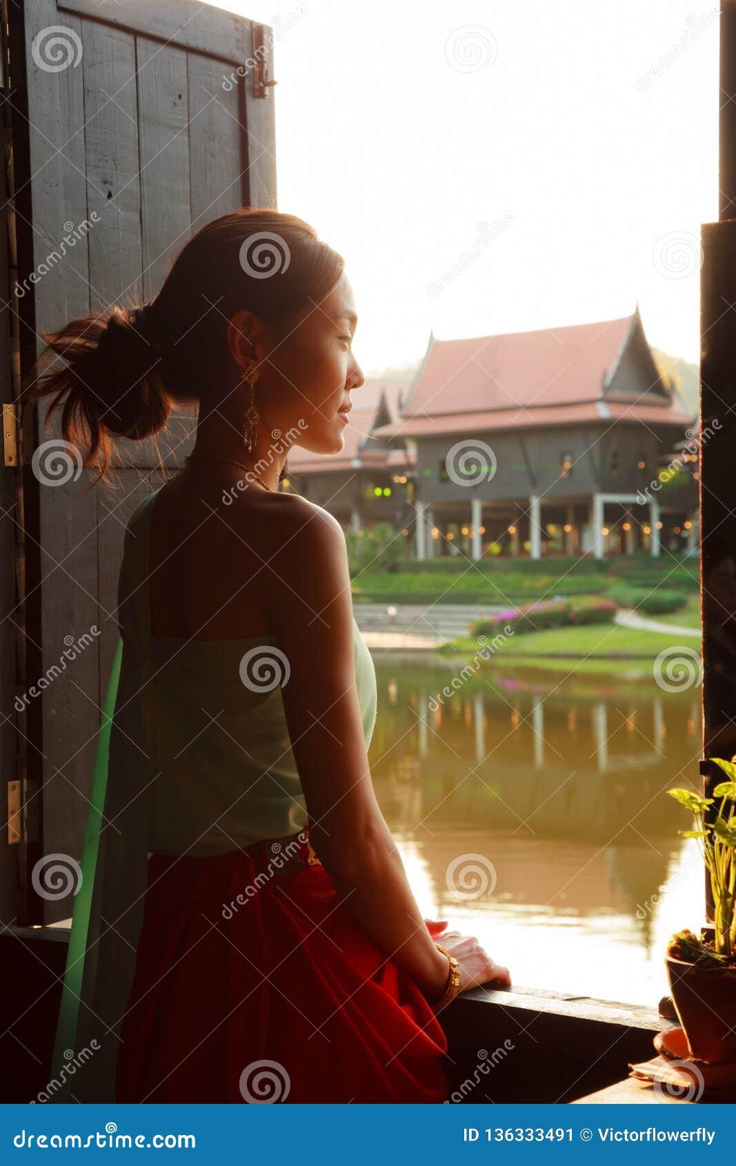 Jonge Mooie Thaise Aziatische vrouw die zich in uitstekend retro Traditioneel Thais kostuum kleden die uit venster kijken Culture