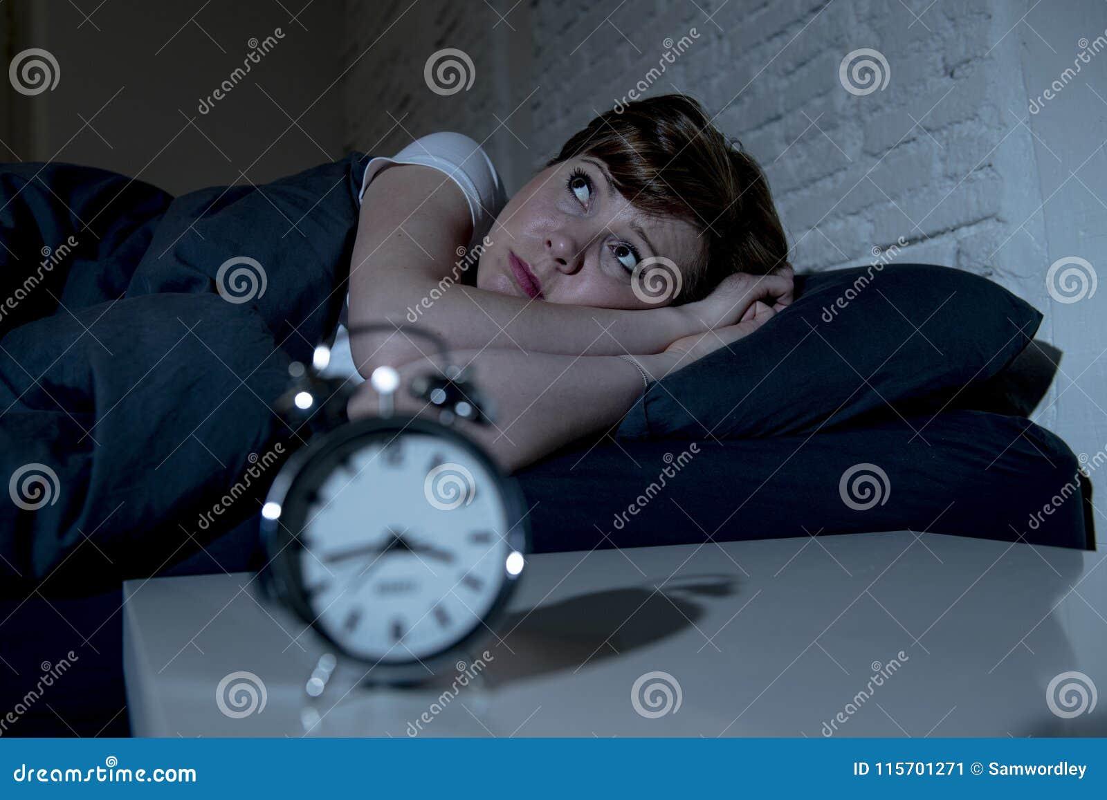 Jonge mooie vrouw die in bed laat bij nacht liggen die aan slapeloosheid lijden die aan slaap proberen