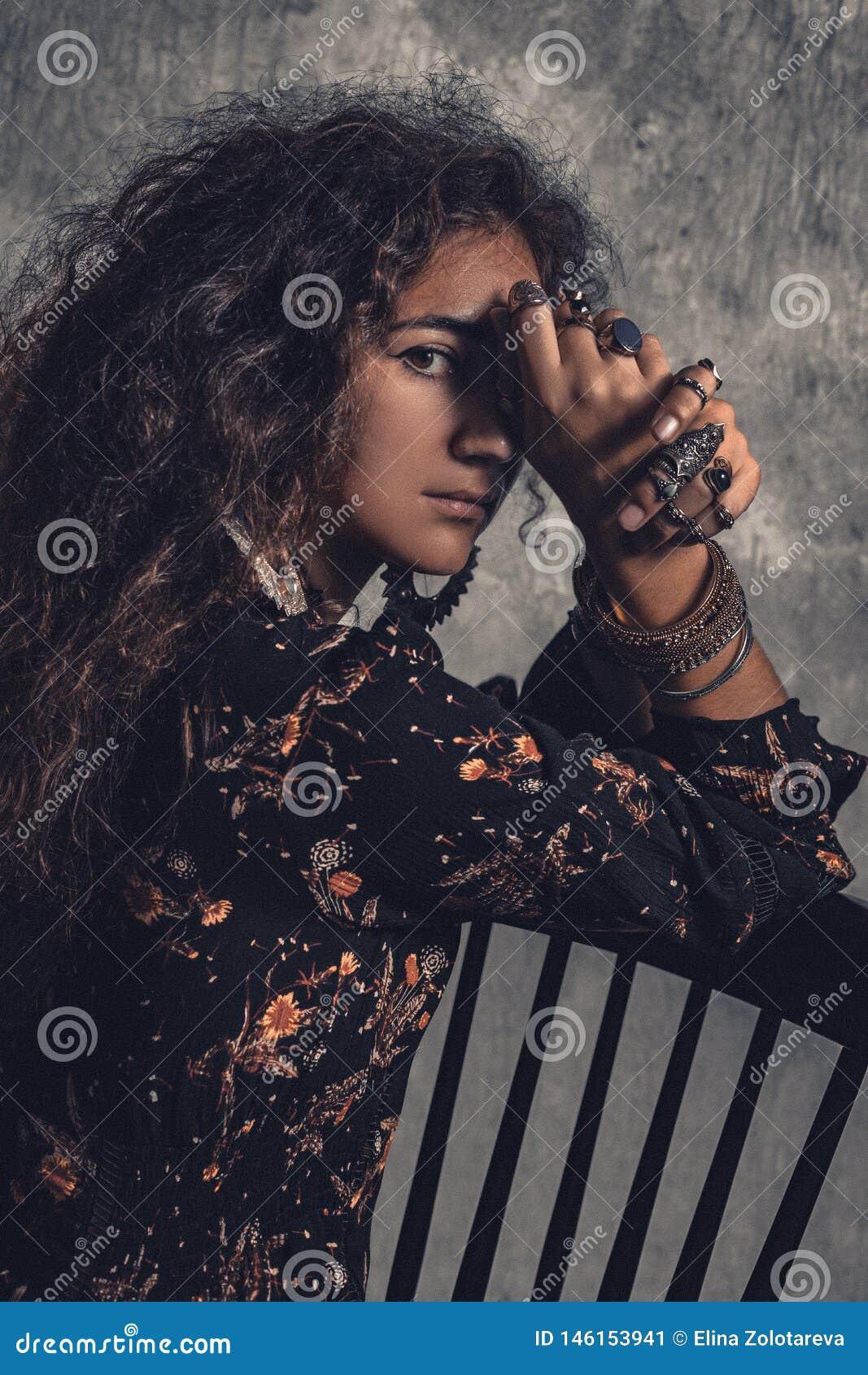 Jonge mooie vrouw die in elegante kleding met bohotoebehoren op stoel zitten