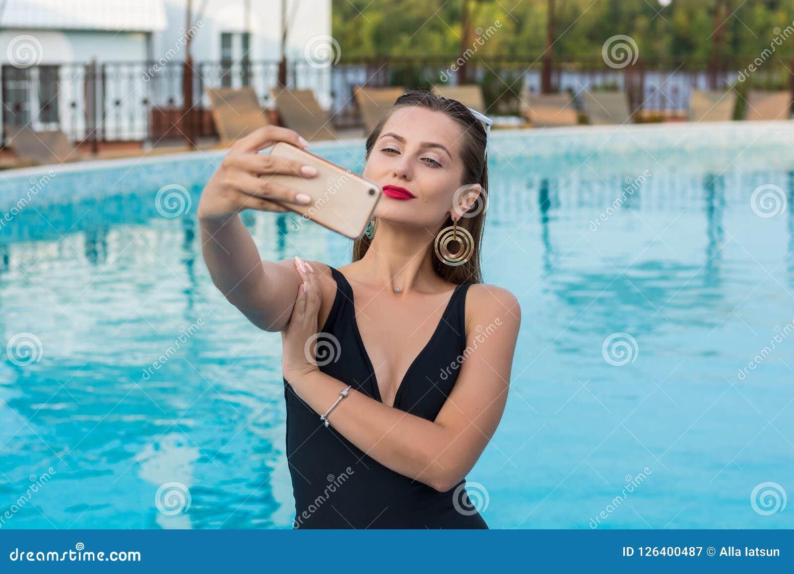 Jonge mooie vrouw die selfie op een smartphone in de pool doen