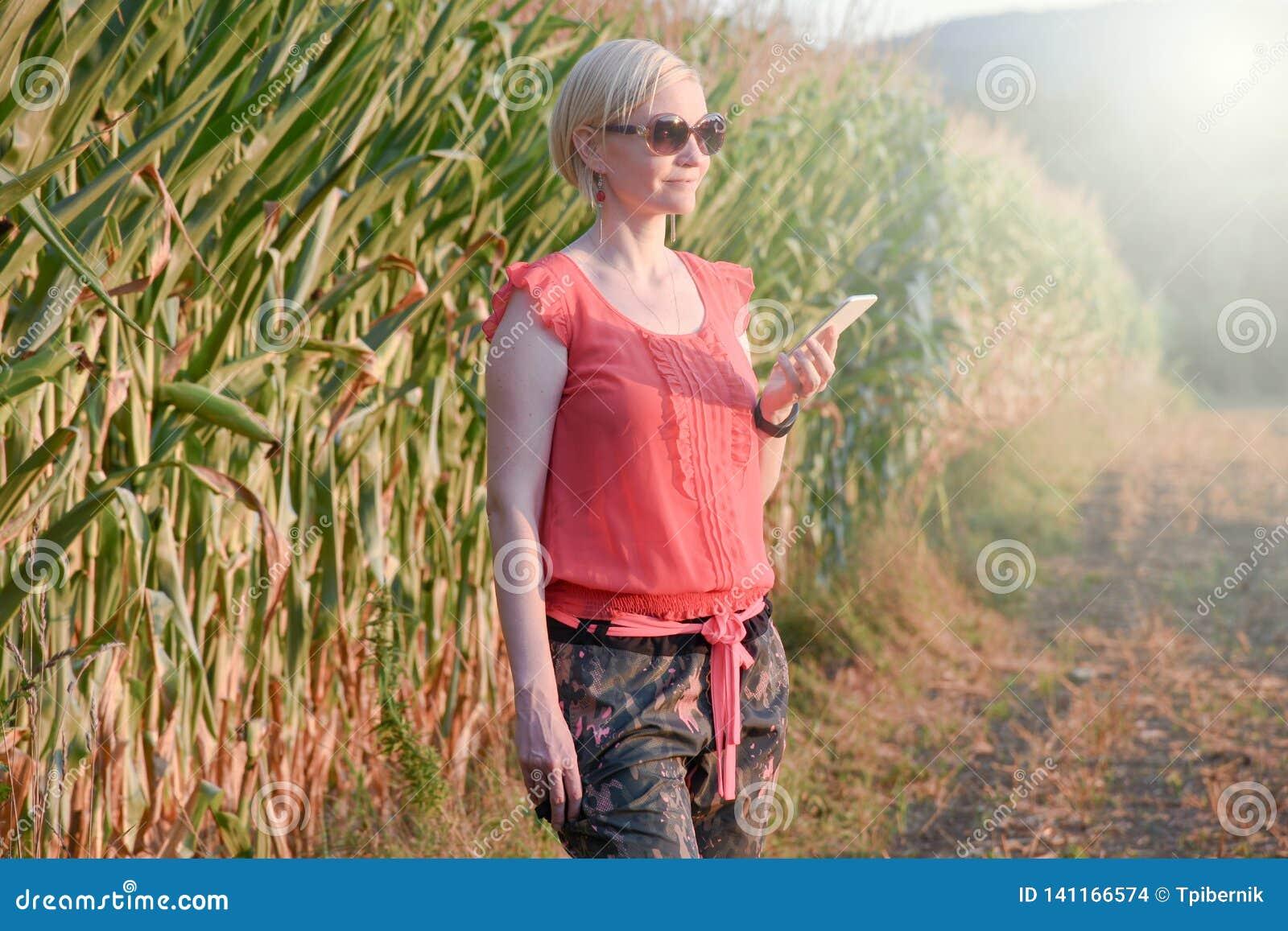 Jonge mooie vrouw in het kleurrijke doeken en zonnebril openlucht spreken op de celtelefoon