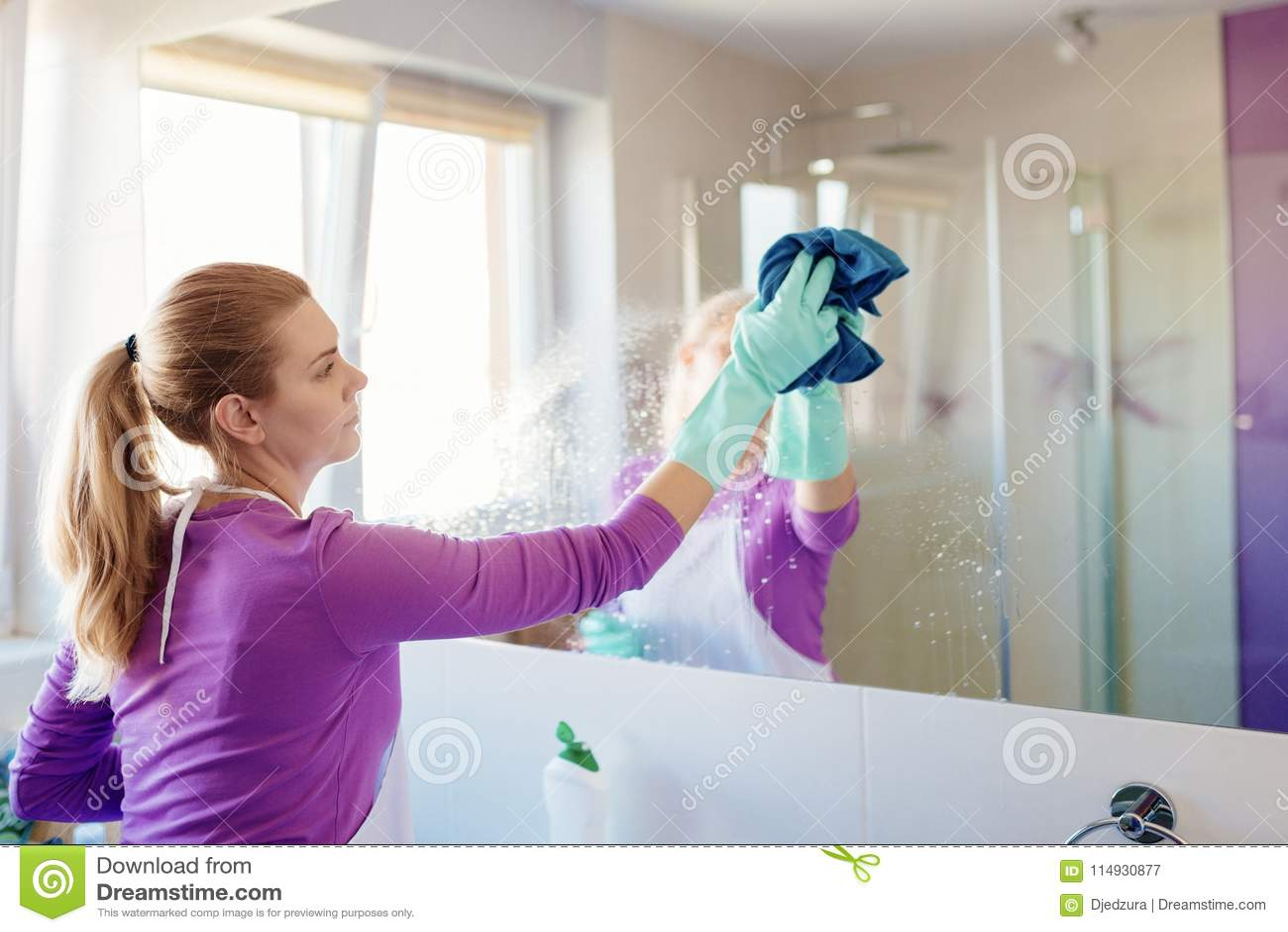 Jonge mooie vrouw in het schoonmaken van spiegel in badkamers