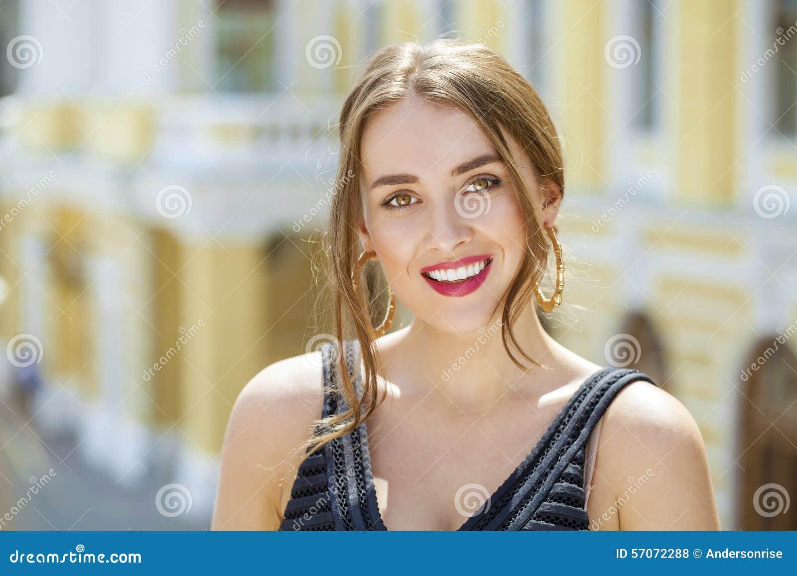 Jonge mooie vrouw in het zwarte kleding stellen in openlucht in zonnig wij