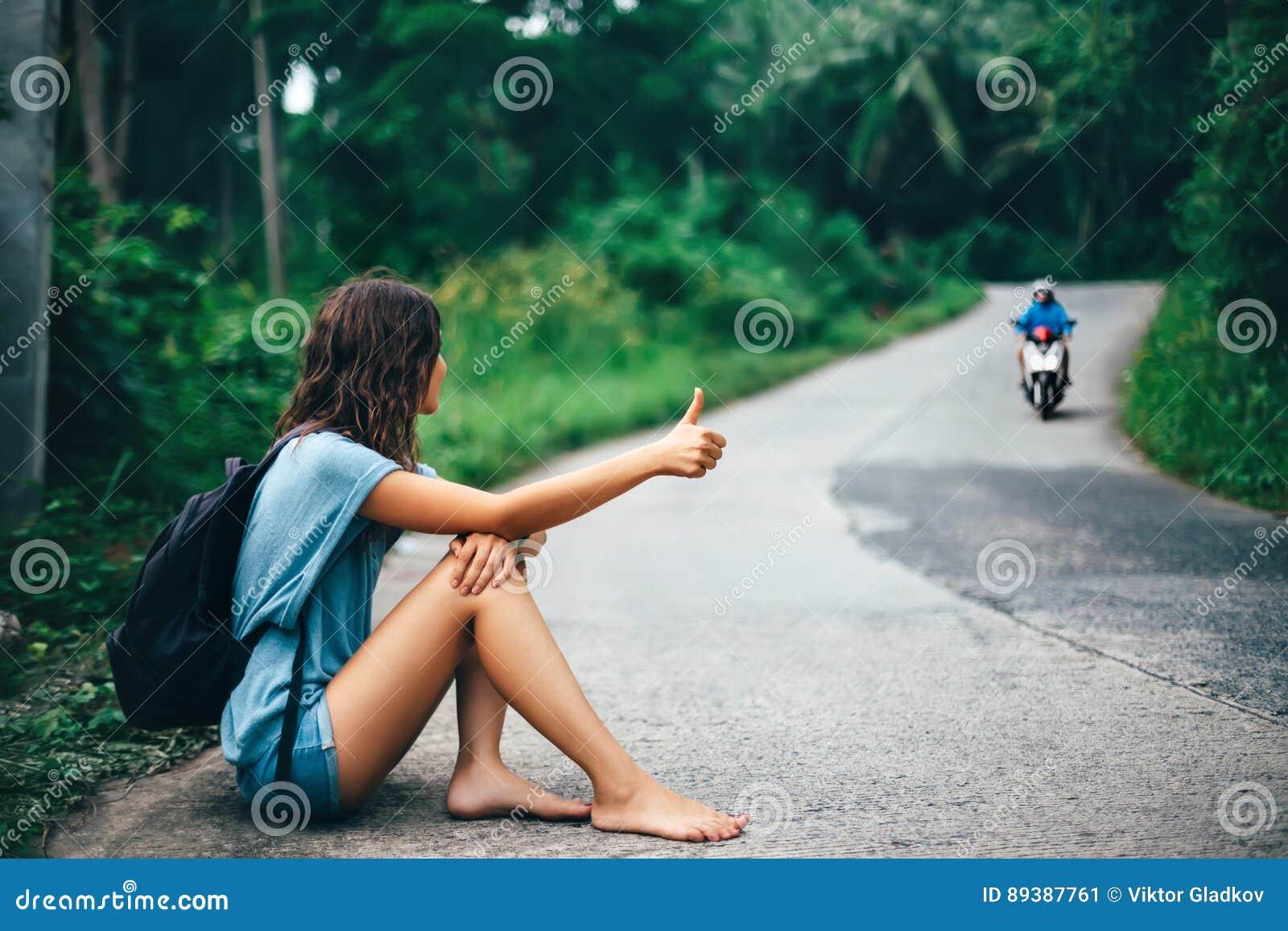 Jonge mooie vrouw liftzitting op weg