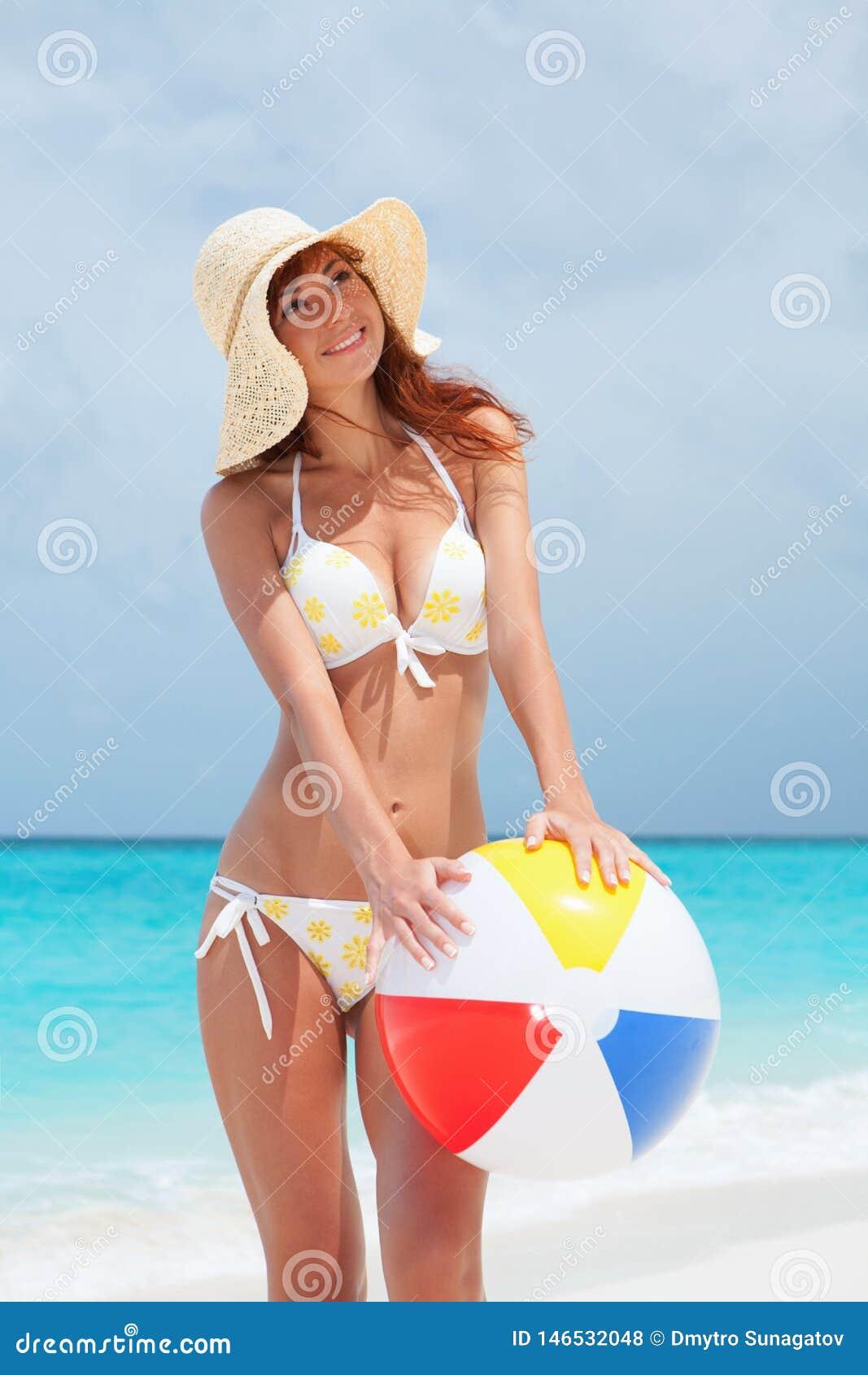 Jonge mooie vrouw met bal op de strandachtergrond Gelukkige Levensstijl Wit zand, blauwe hemel en kristaloverzees van tropisch st