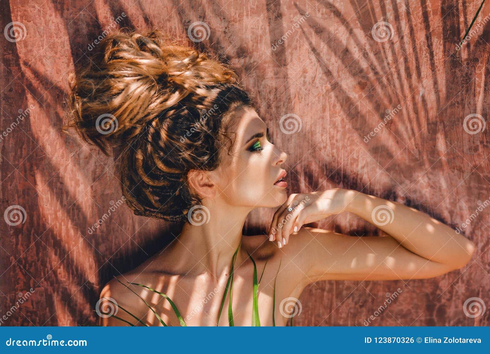 Jonge mooie vrouw met schaduwen op gezicht met gesloten ogen