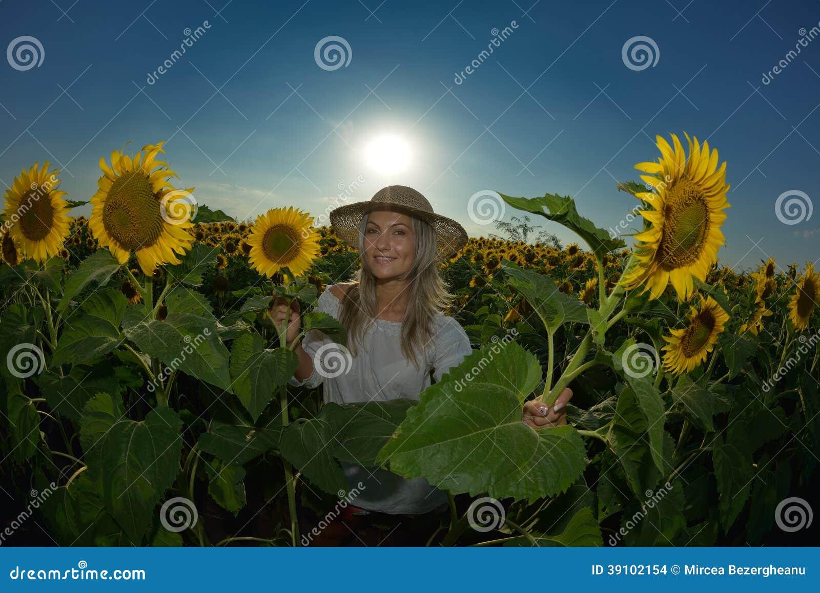 Jonge mooie vrouw op zonnebloemgebied