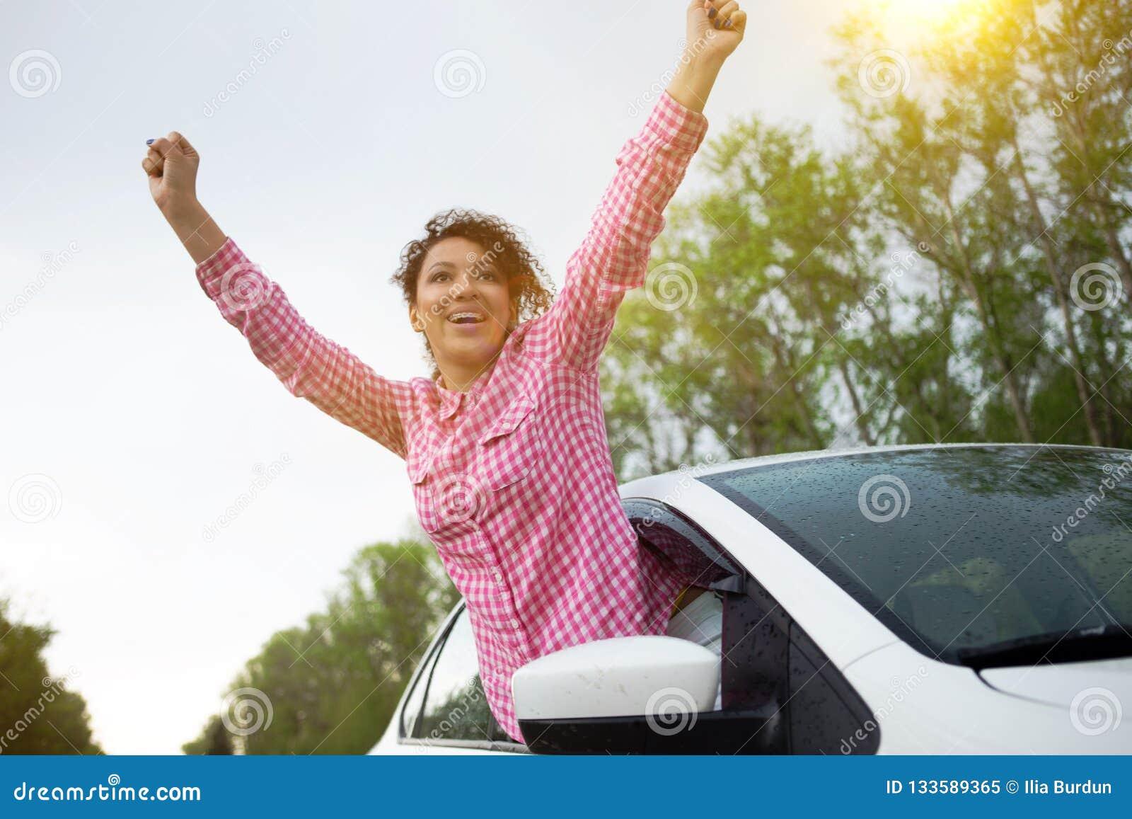 Jonge mooie vrouwen drijfauto en het leunen uit autoraam reizend door auto, de zomervakantie