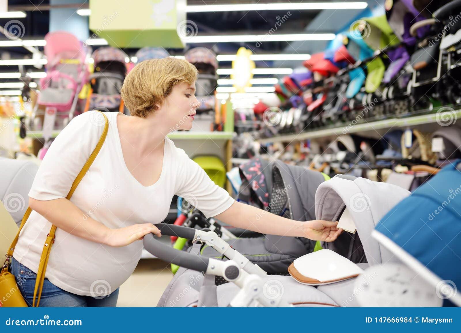 Jonge mooie zwangere vrouw babywandelwagen kiezen of kinderwagen die met fouten voor pasgeboren Het winkelen voor aanstaande moed
