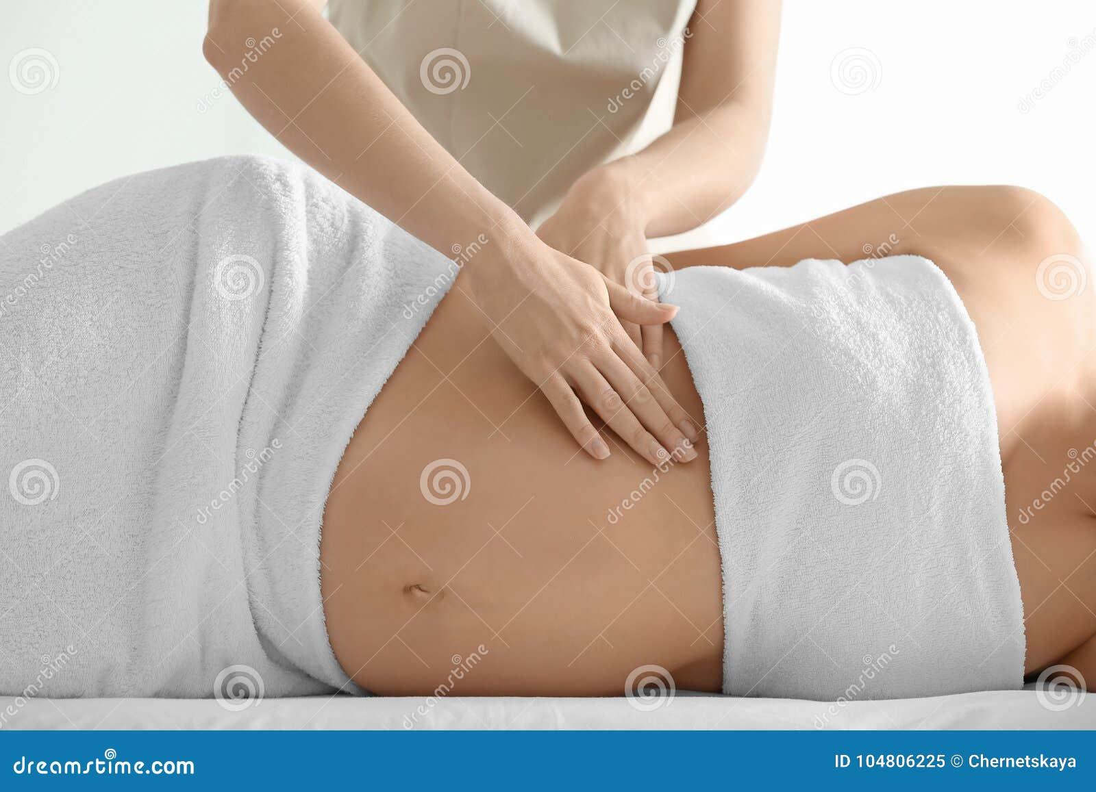 Jonge mooie zwangere vrouw die massage hebben