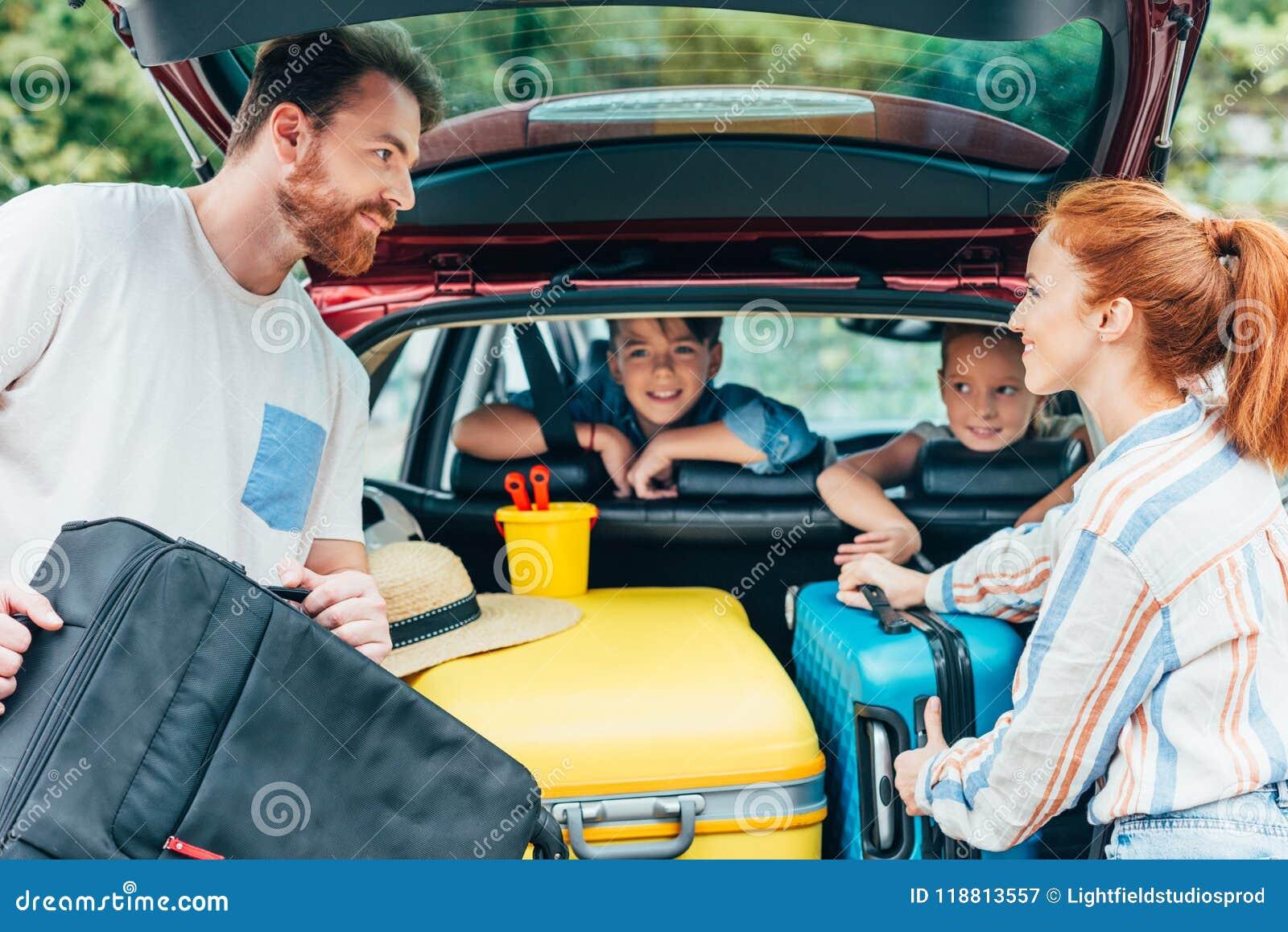 Jonge ouders die bagage in boomstam van auto met jonge geitjes inpakken