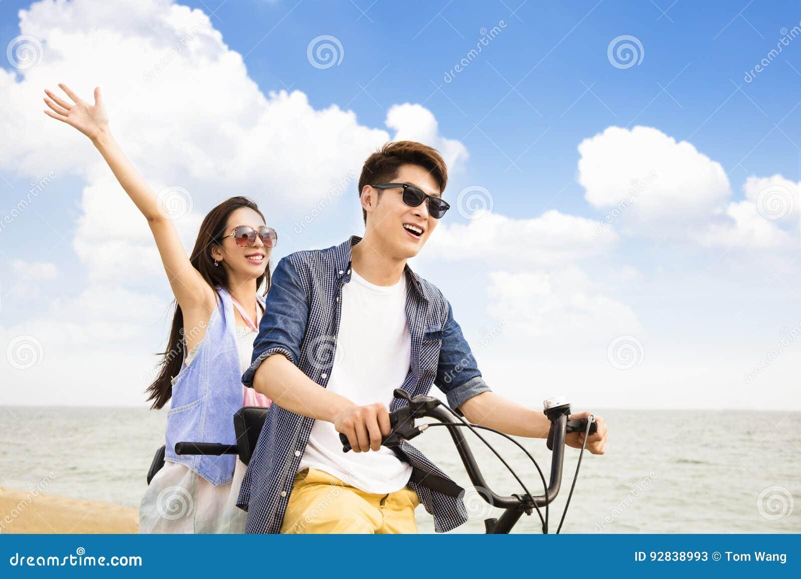 Jonge paar berijdende fiets op het strand