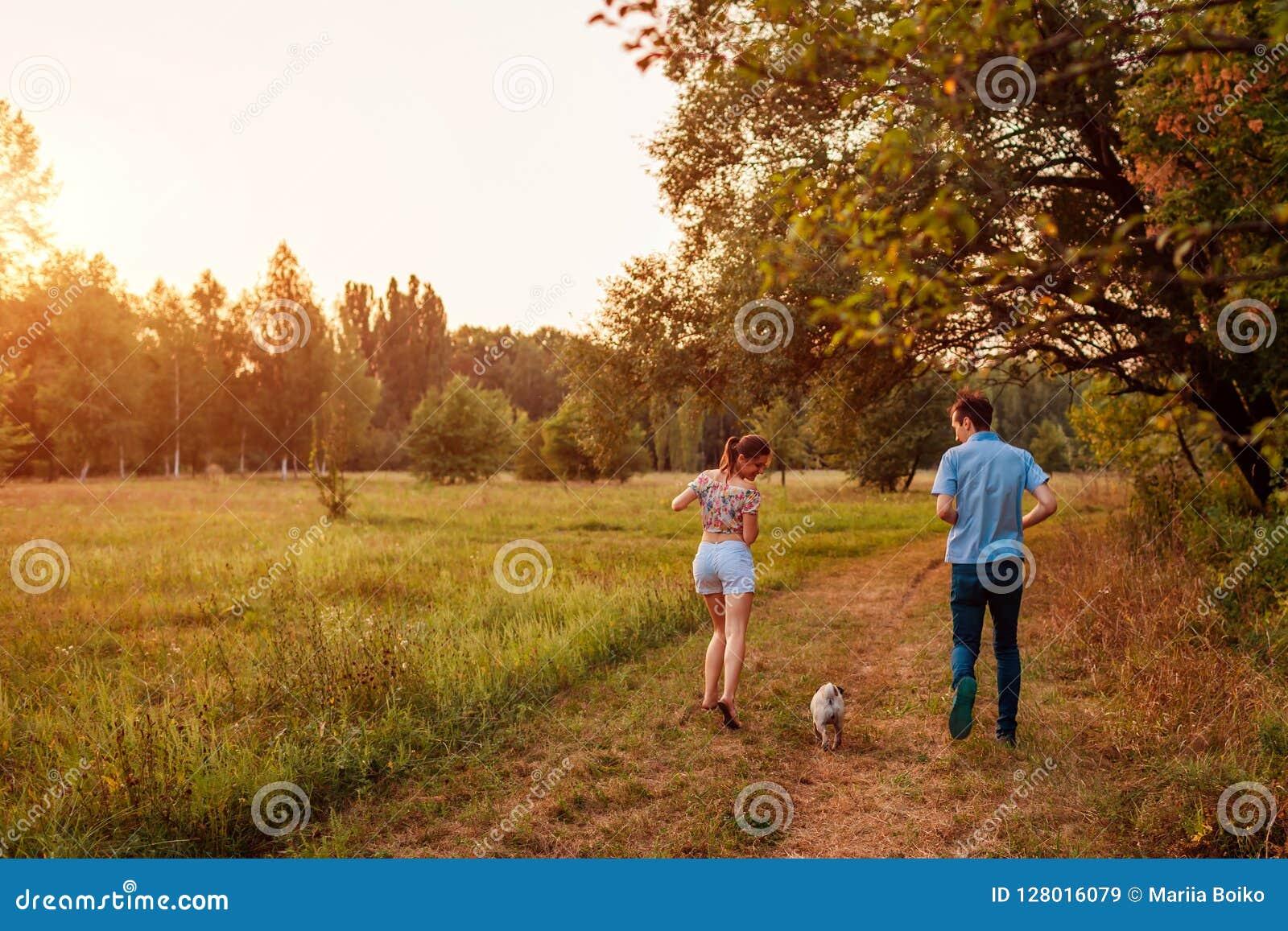 Jonge paar het lopen pug hond in de herfst bos Gelukkig puppy die en pret het spelen met meester in werking stellen hebben