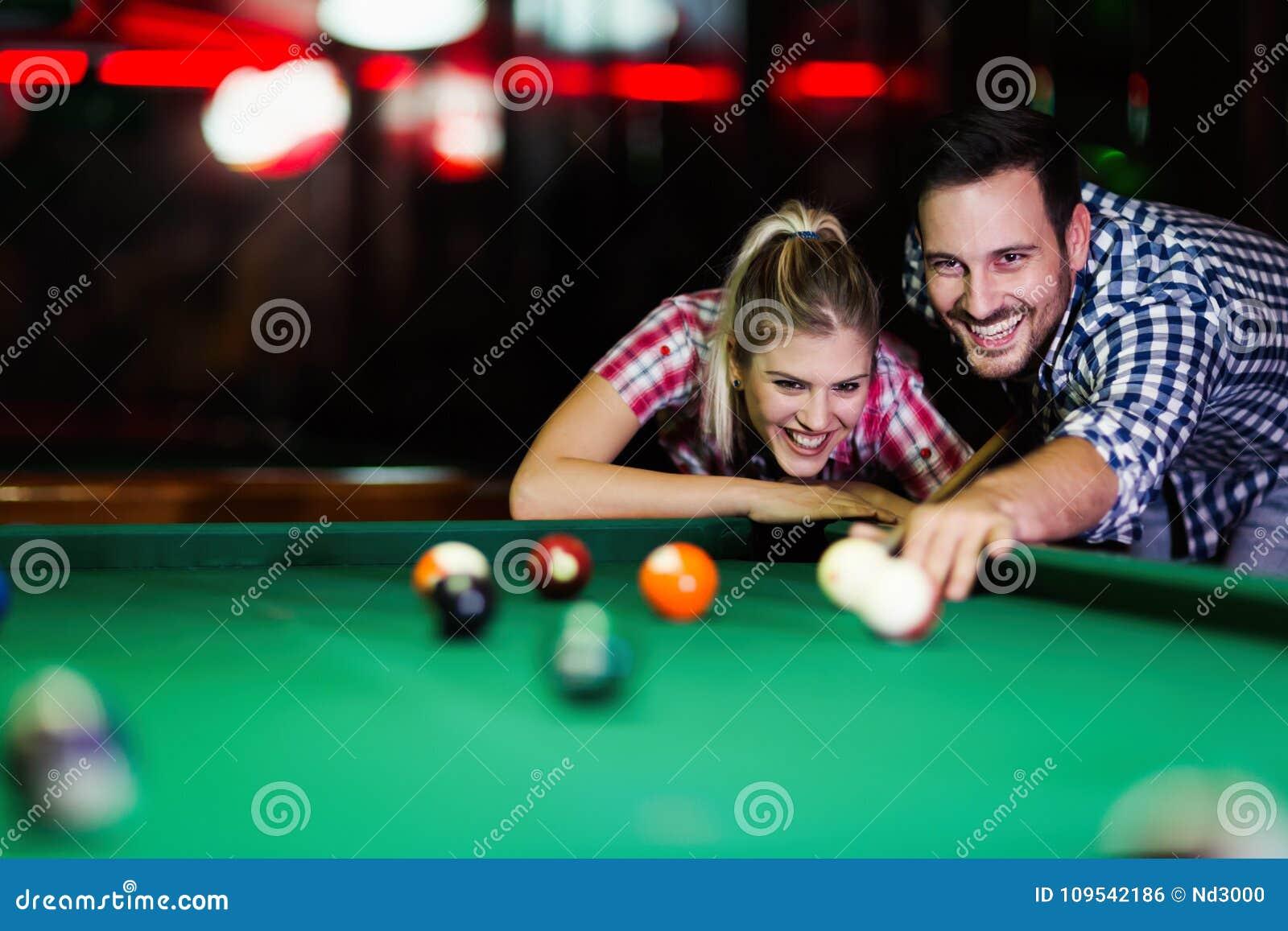 Jonge paar het spelen snooker samen in bar