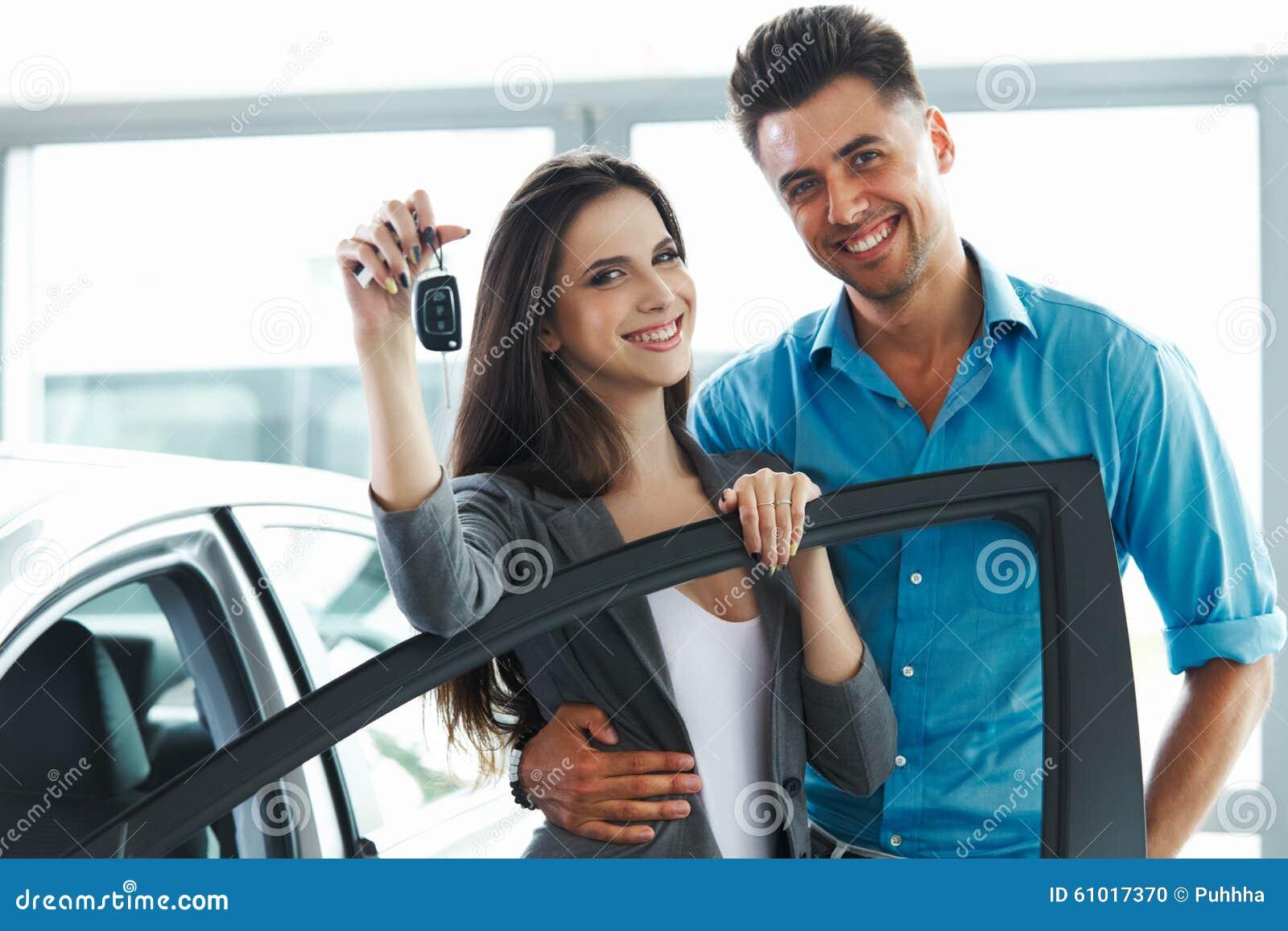 Jonge Paar het Vieren Aankoop van een auto in Autotoonzaal