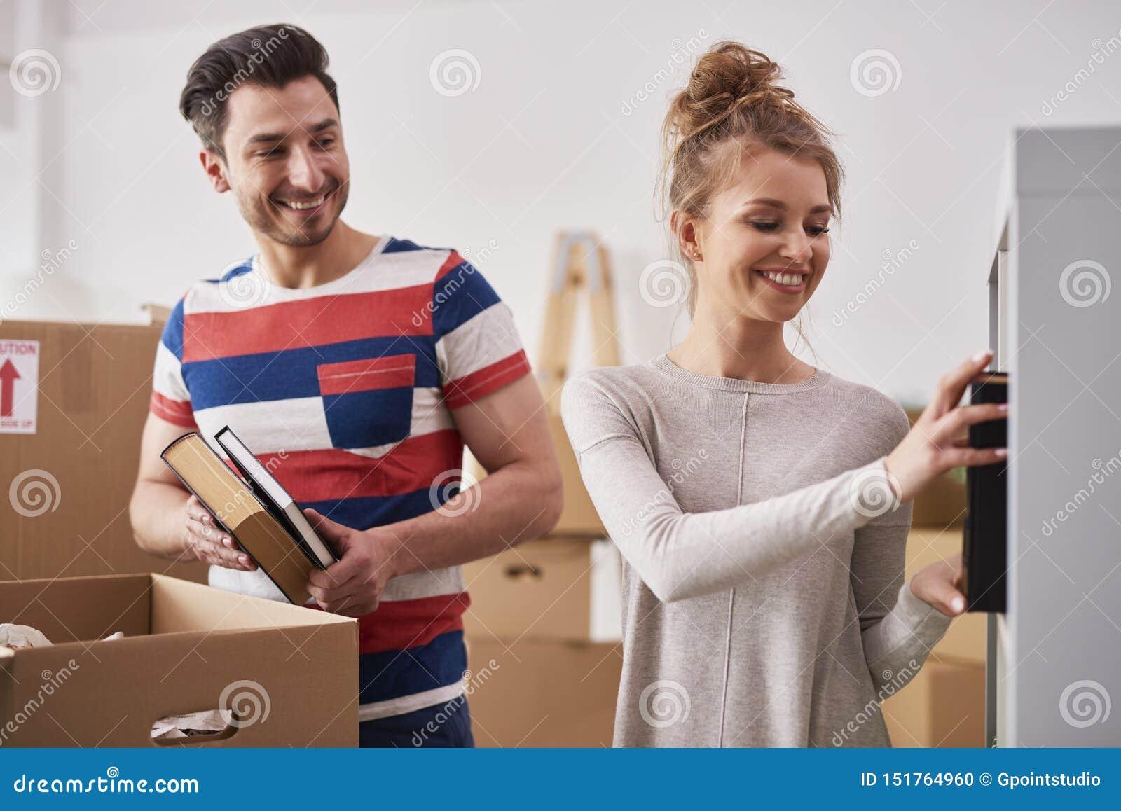Jonge paar uitpakkende bewegende dozen in nieuwe vlakte