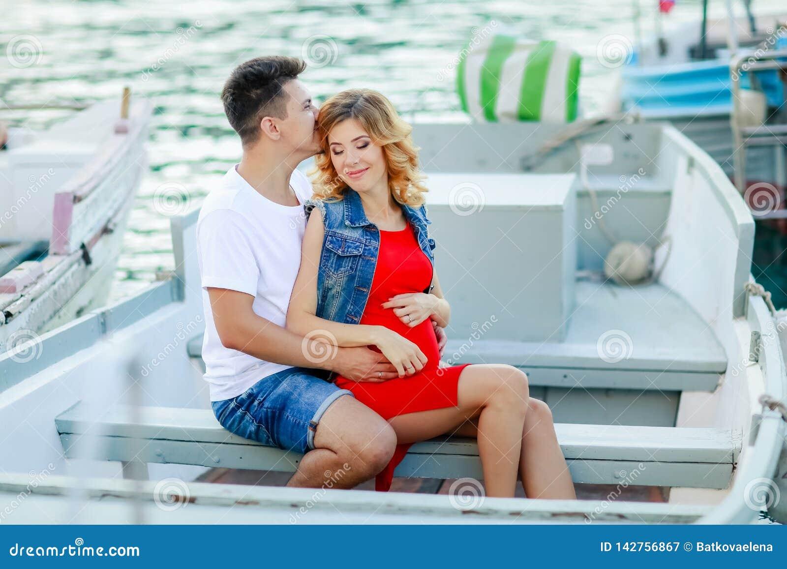 Jonge paaromhelzingen en het ontspannen bij dok dichtbij boot, op zonnige de zomerdag De vrouw en de man in modieuze kleren bevin