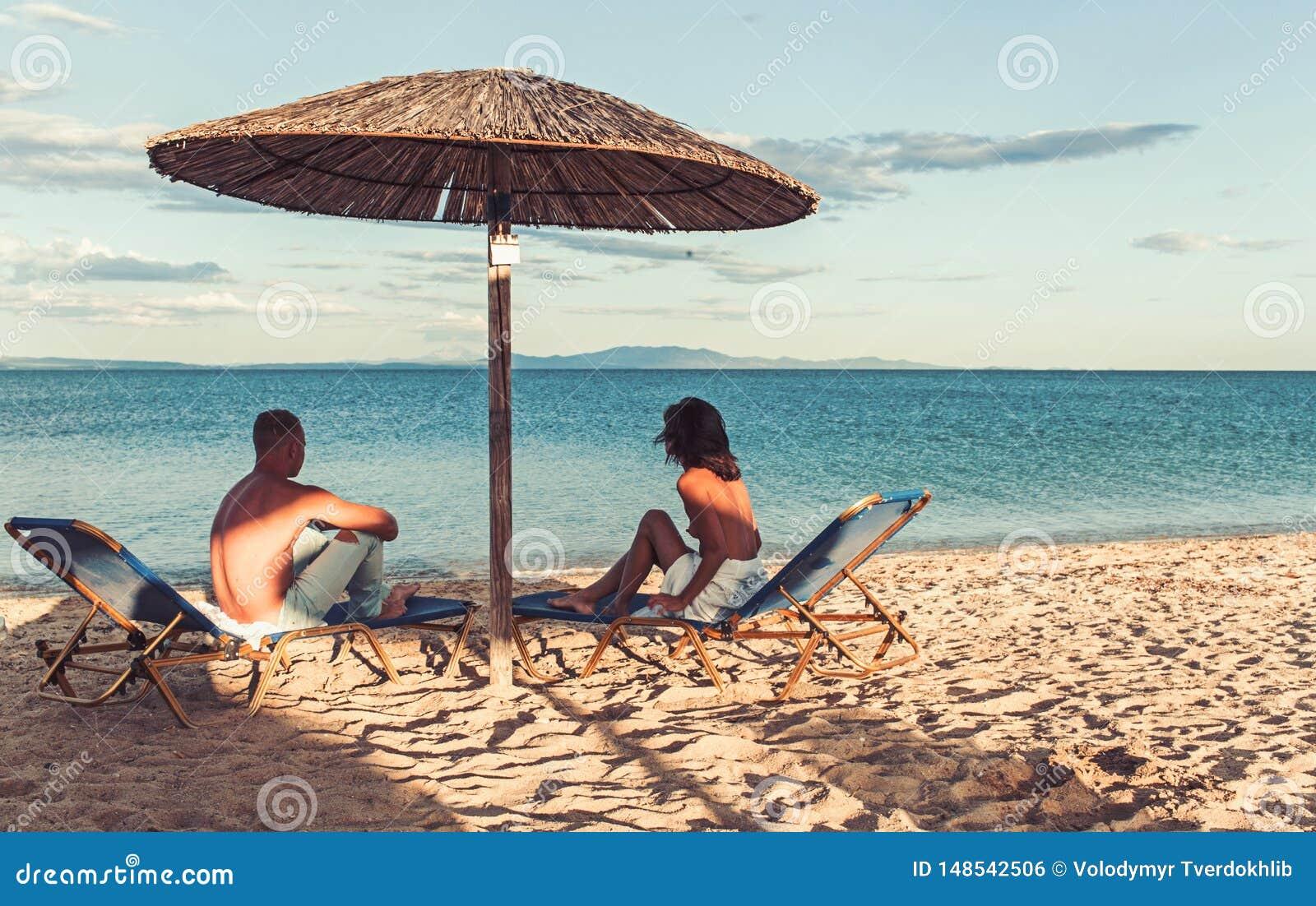 Jonge paarzitting op een tropisch zandig strand onder paraplu