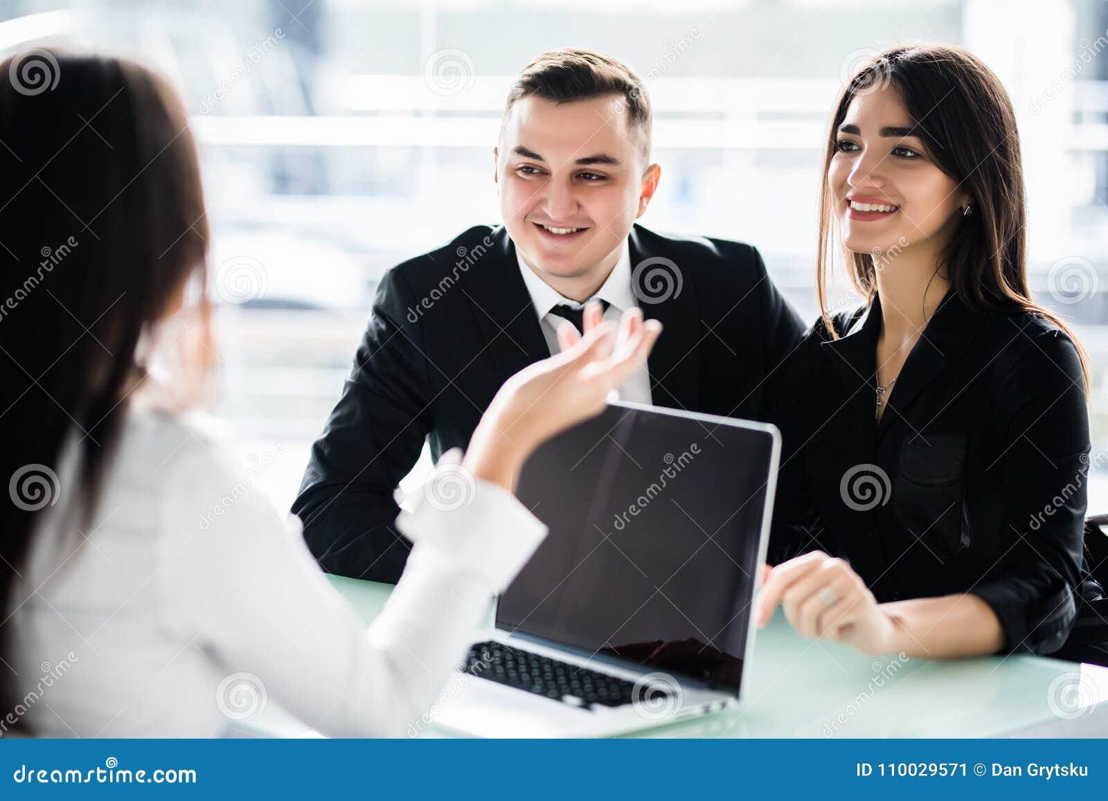 Jonge paarzitting samen bij het bureau en het luisteren aan hun financiële adviseur