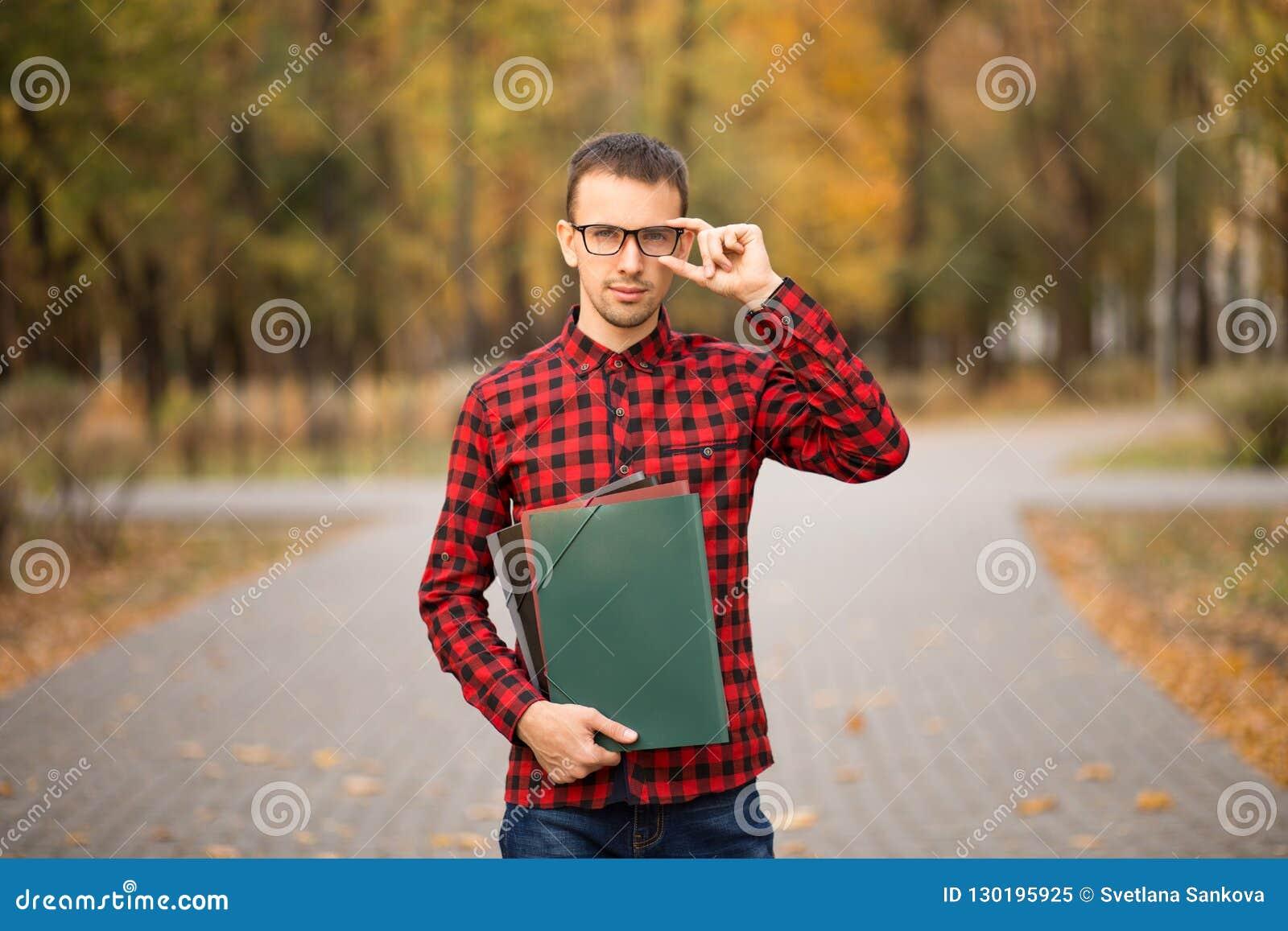 Jonge professor die in glazen omslagen in de herfstpark houden