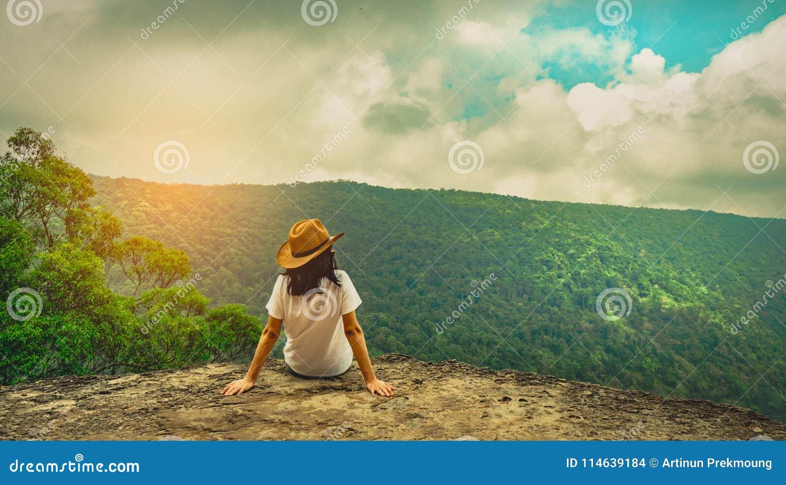 Jonge reizende vrouw die hoed dragen en op de bovenkant van de bergklip zitten met het ontspannen van stemming Aziatische vrouwen