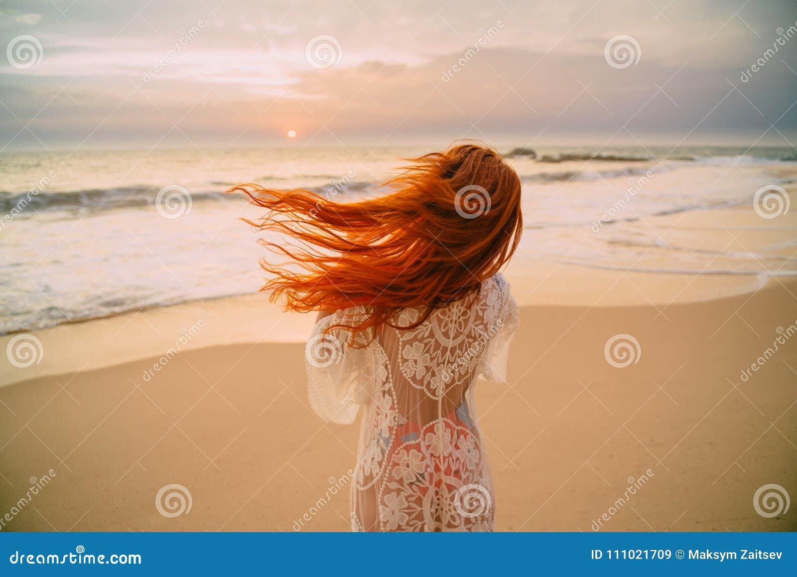 Jonge roodharige vrouw met vliegend haar op de oceaan, achtermening