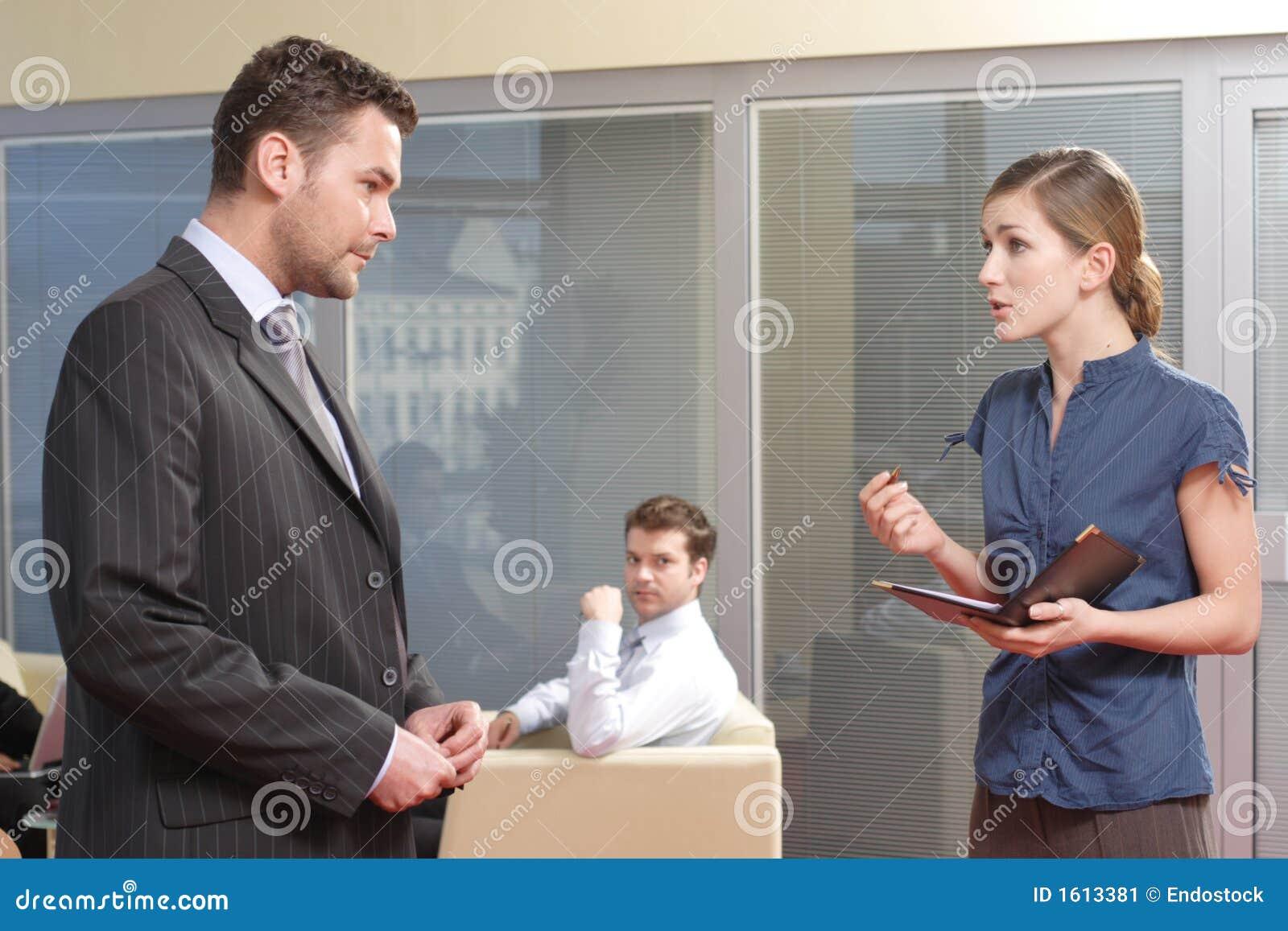 Jonge secretaresse die aan haar werkgever in het bureau spreekt