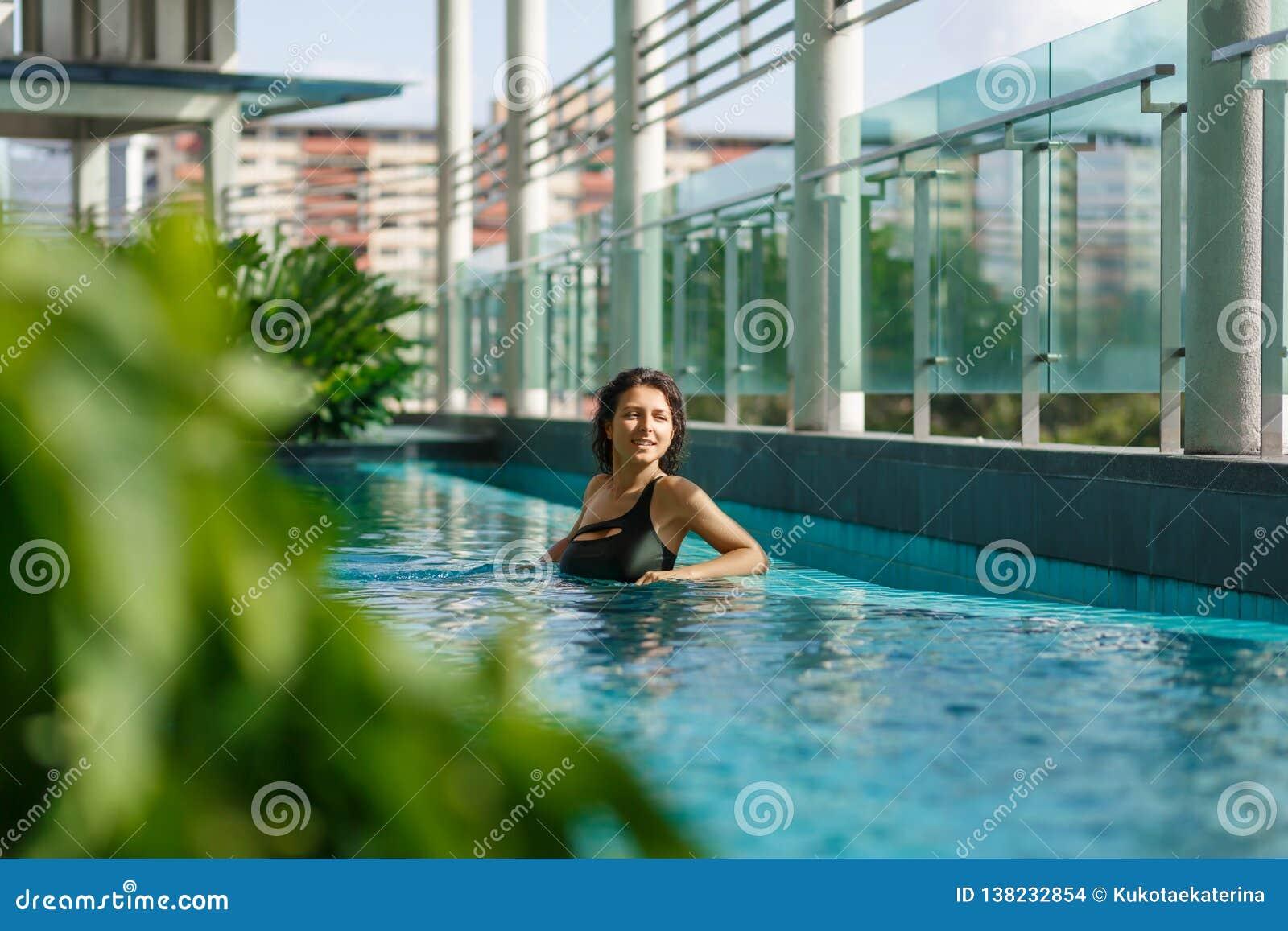 Jonge sexy Kaukasische vrouw die in zwempak op stadslandschap kijken van dak zwembad met groene bomen
