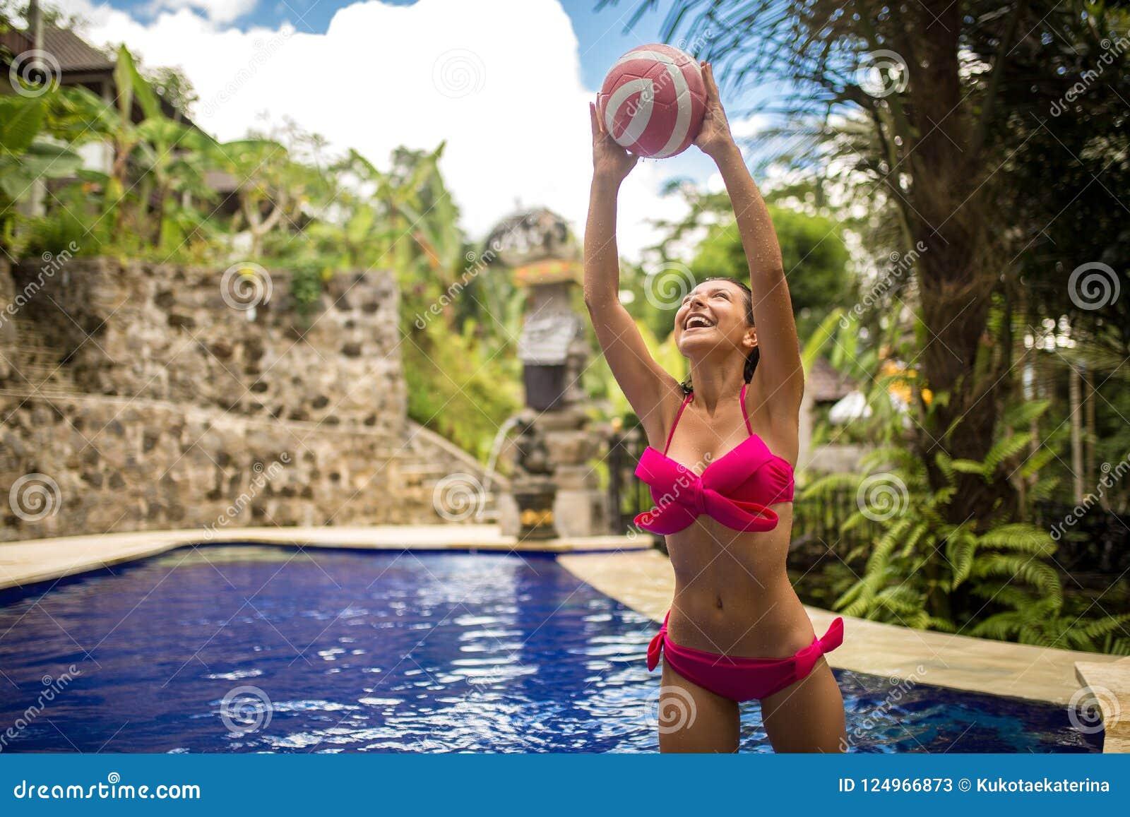 Jonge sexy vrouw in roze zwempakspel met bal in tropische swimpool Bij mooie Balinesse-wildernisachtergrond