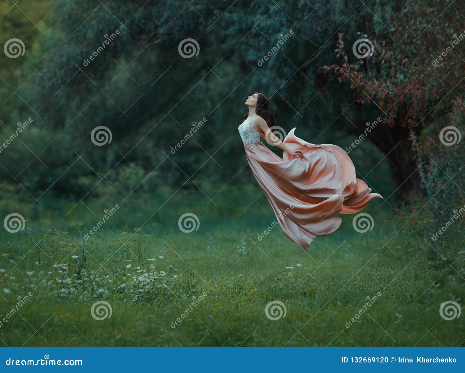 Jonge slanke vrouw met donker haar en keurige haar geklede lange luxueuze golvende vliegende kleding omhoog in de lucht iFreedom,
