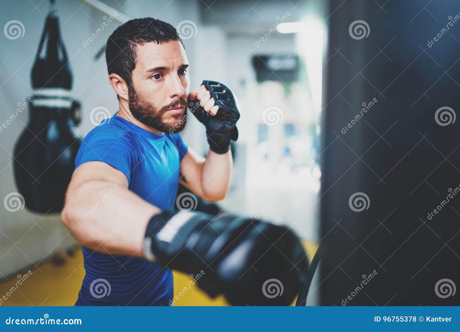 Jonge spier kickboxing vechter het praktizeren schoppen met ponsenzak Schopbokser het in dozen doen als oefening voor de strijd b