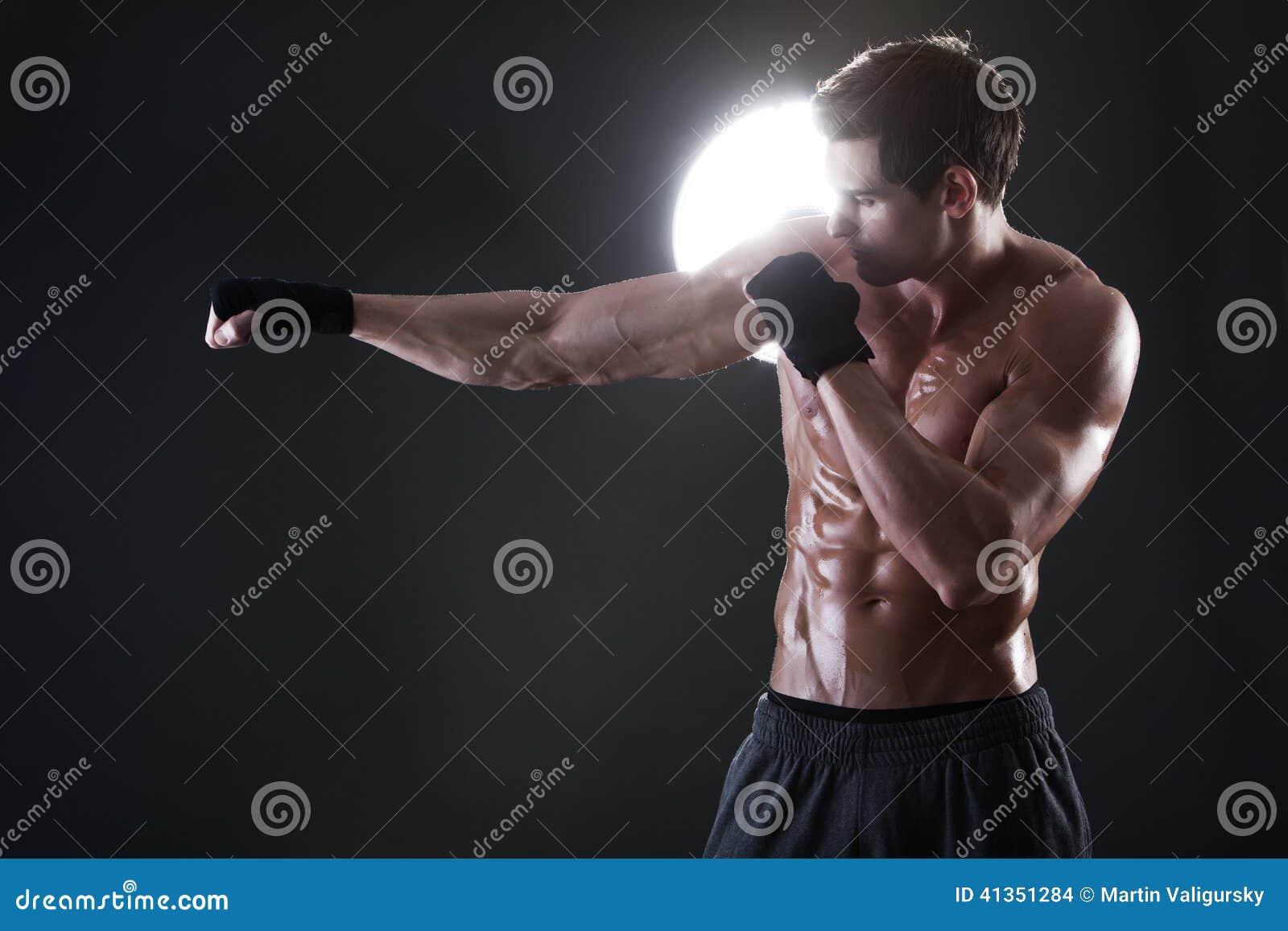 Jonge spierkerel met het naakte torso in dozen doen