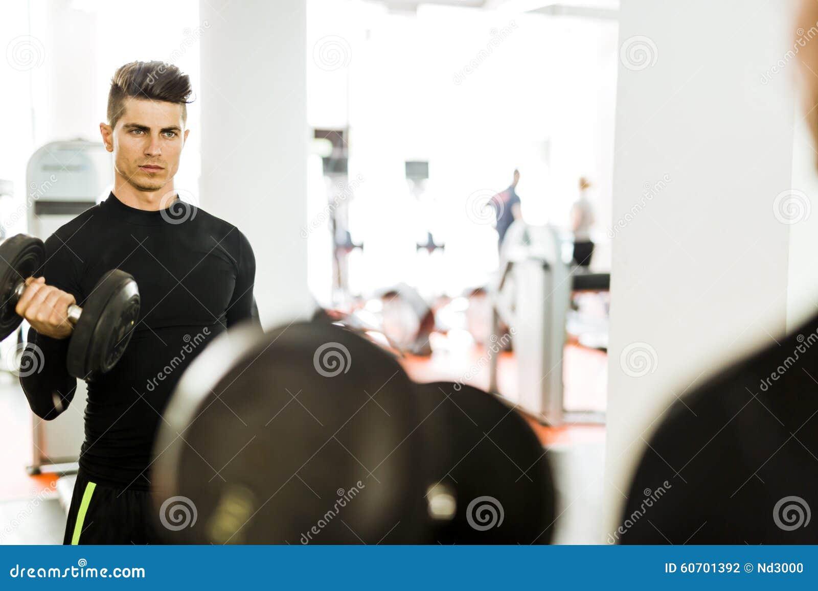 Jonge spiermens die in een gymnastiek en het opheffen gewichten uitwerken
