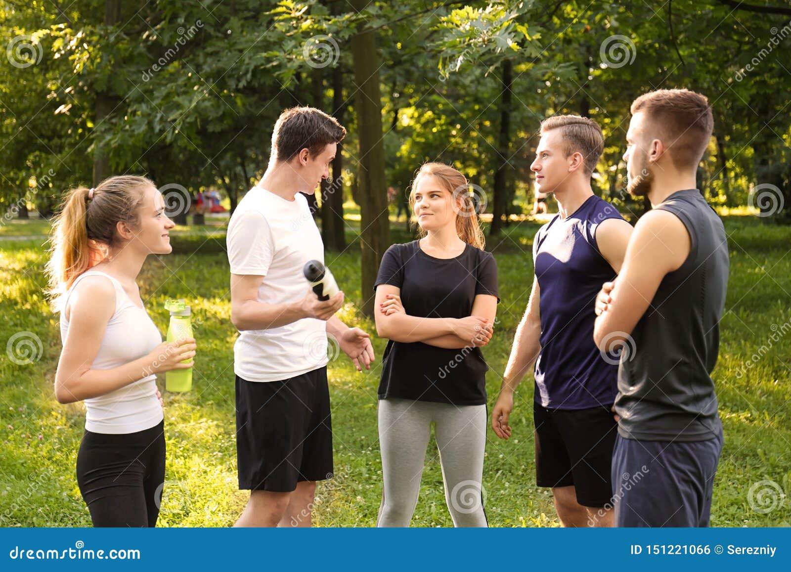 Jonge sportieve mensen die rust na in openlucht opleiding hebben