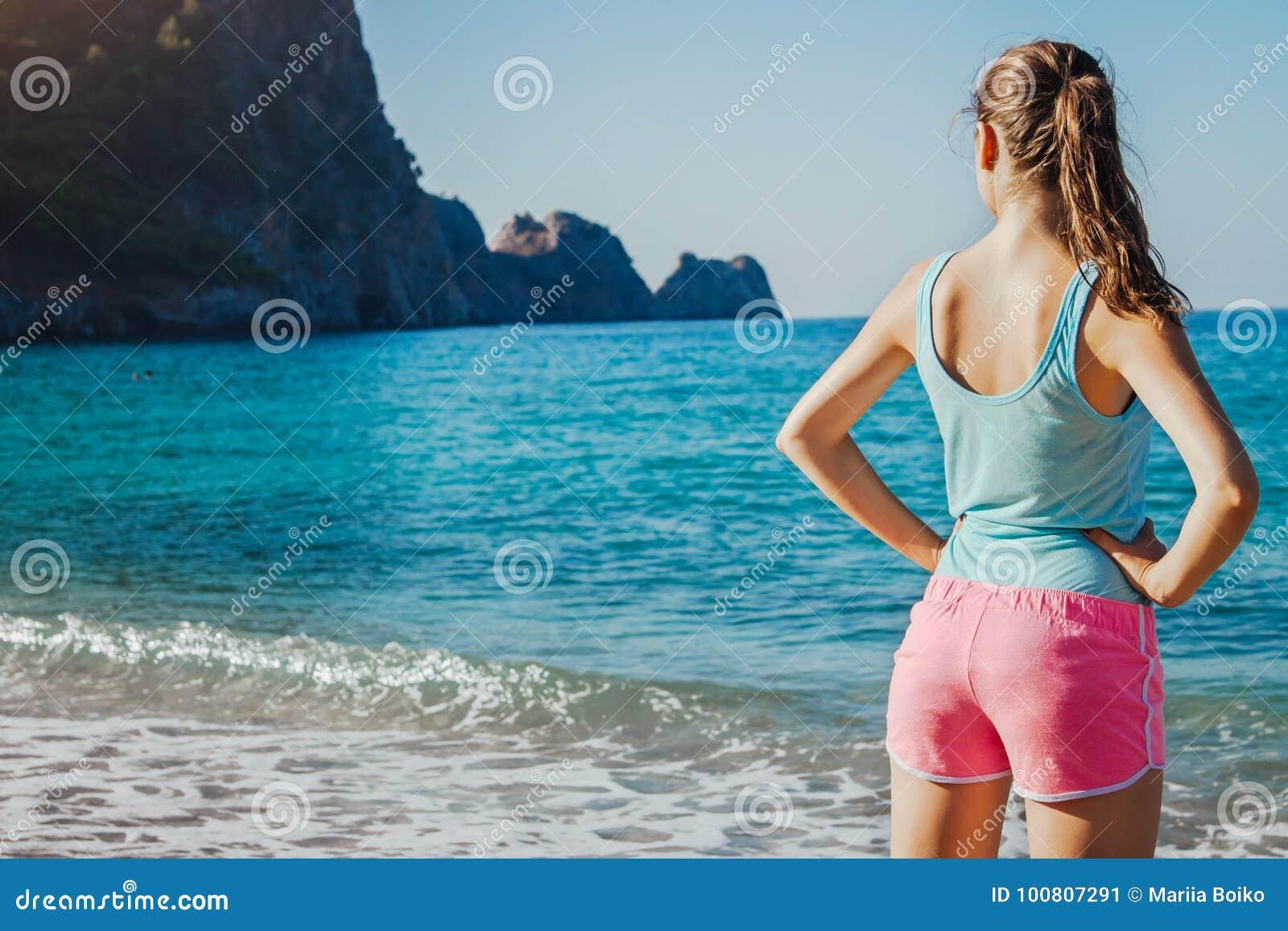 Jonge sportieve vrouw die een rust na een training op het strand hebben
