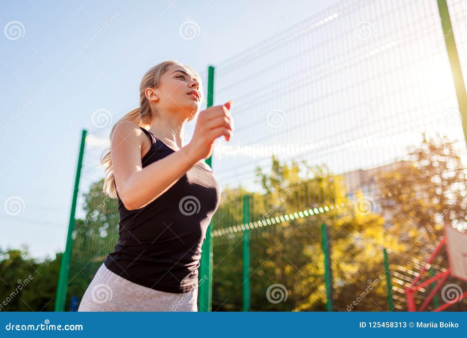 Jonge sportieve vrouwenatleet die op sportsground in de zomer lopen In openlucht het aanstoten Gezonde manier van het leven