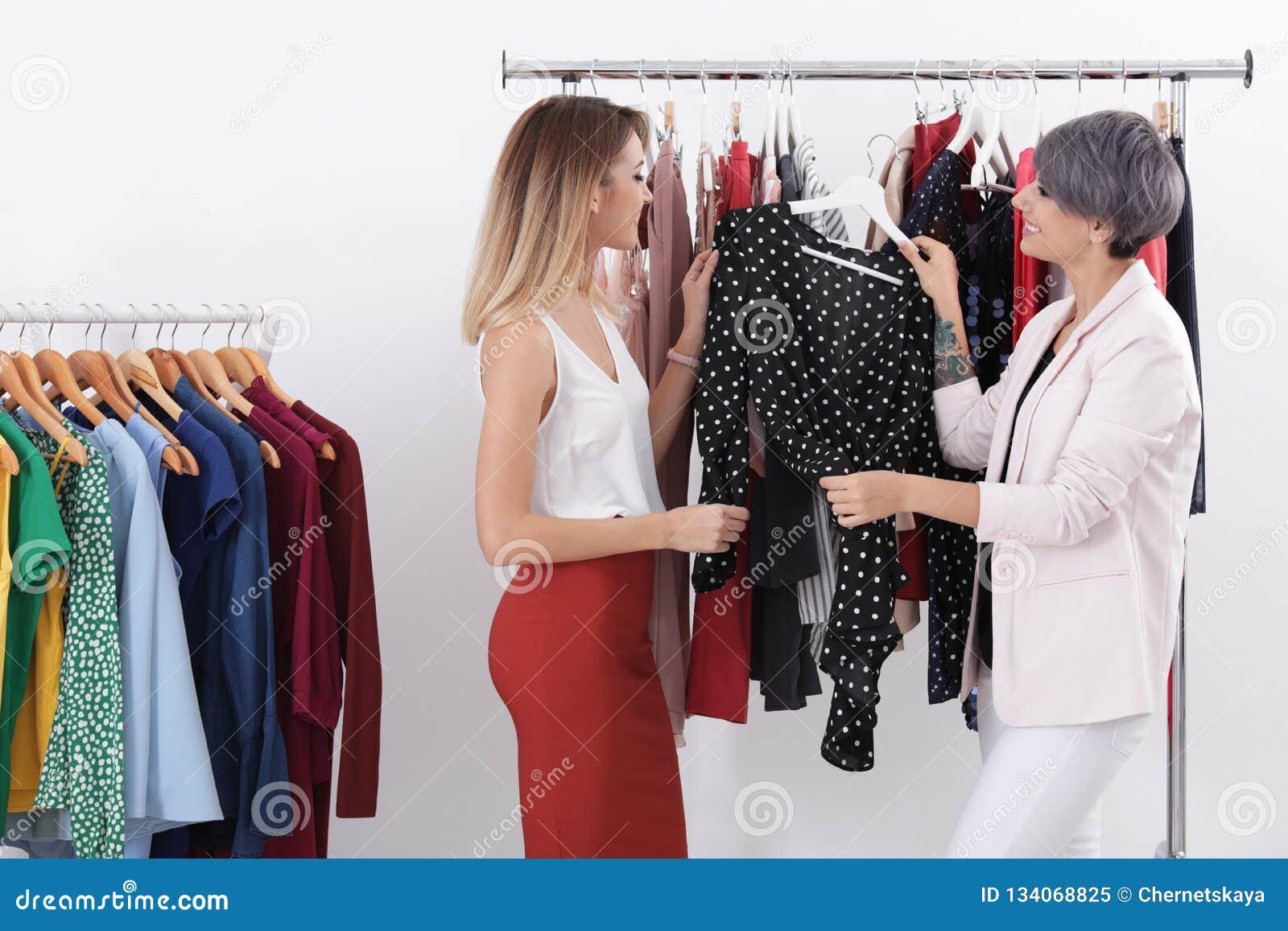 Jonge stilist die cliënt helpen om in kleren te kiezen