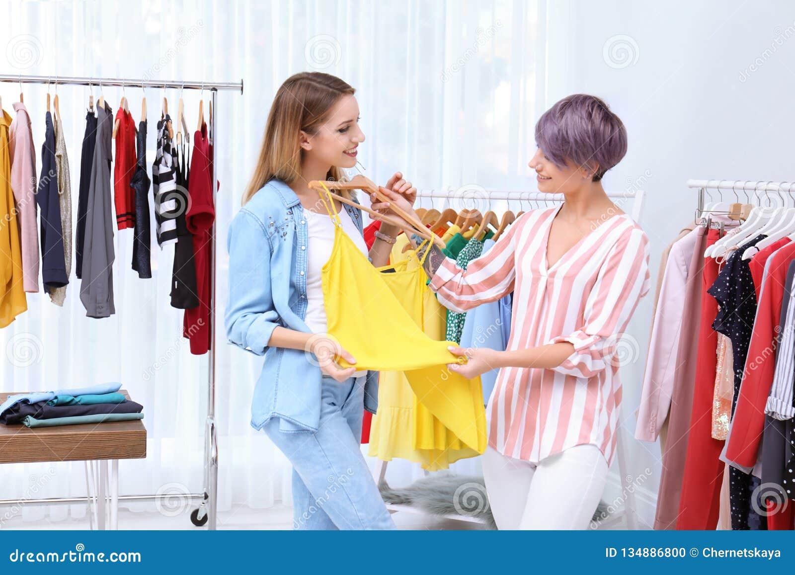Jonge stilist die klant helpen om kleren te kiezen