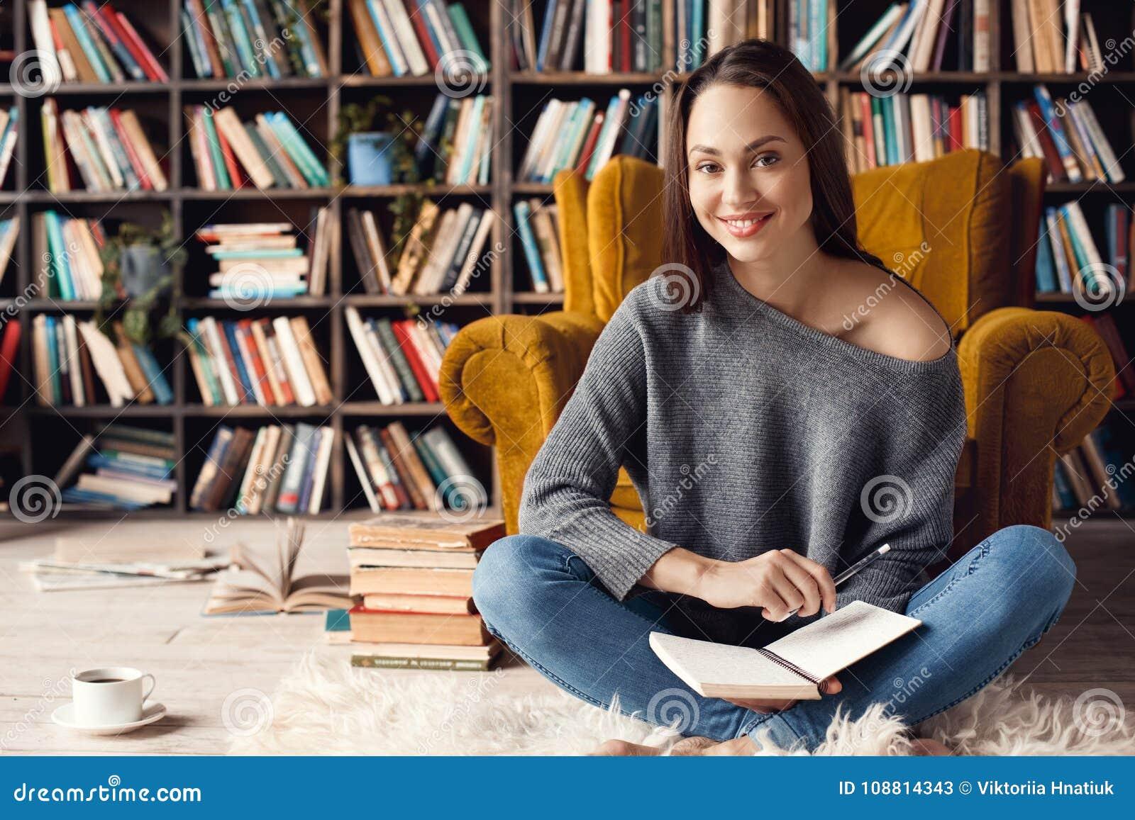 Jonge studente in bibliotheek die thuis het kijken zitten vrolijke camera