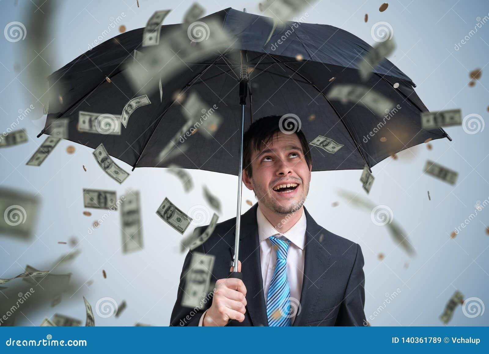 Jonge succesvolle rijke zakenman met paraplu en geld die neer vallen